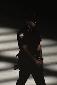 Police man standing faced in darkness