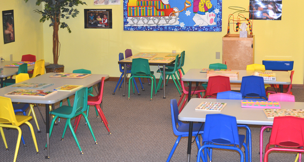 Group desks with colorful chairs where students work together on different activities