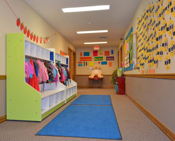 Hallway with childrens' belongings neatly tucked away in cubbies and decorations cover the walls.
