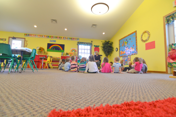 A 3K class sitting in a circle on the floor for story time