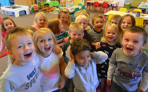 A group of 3K students gather around the camera with big smiles