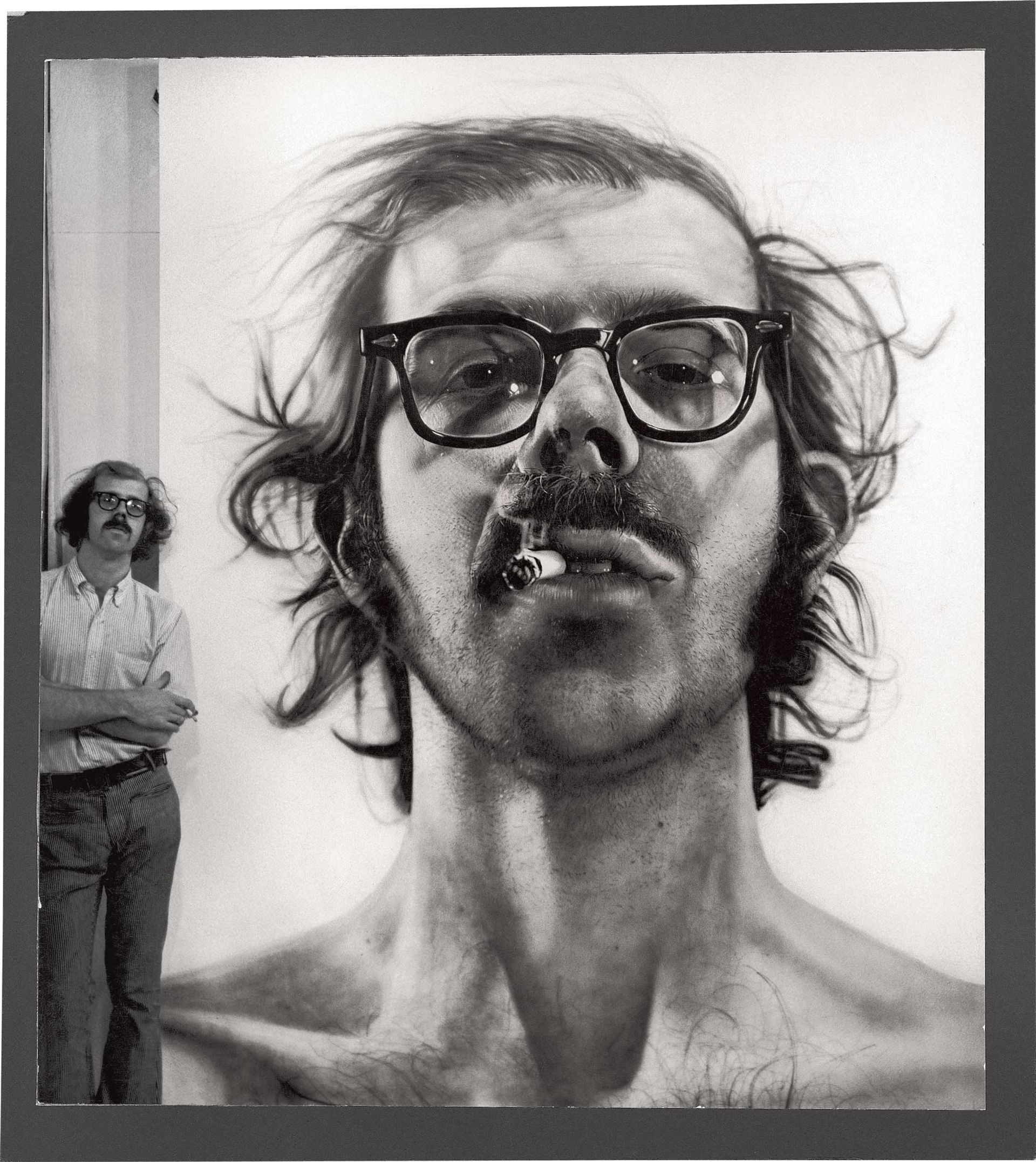 Chuck Close standing next to his Big Self-Portrait (1967–68), acrylic on gessoed canvas