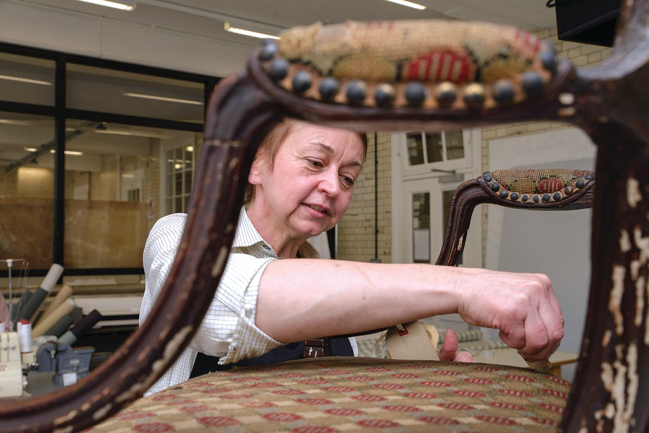 Isobel Harcourt works on the disintegrating upholstery and flaking paint of a Georgian chair, one of around 250,000 V&A objects being catalogued and conserved before the museum vacates its Blythe House stores at the end of 2022 © Victoria and Albert Museum