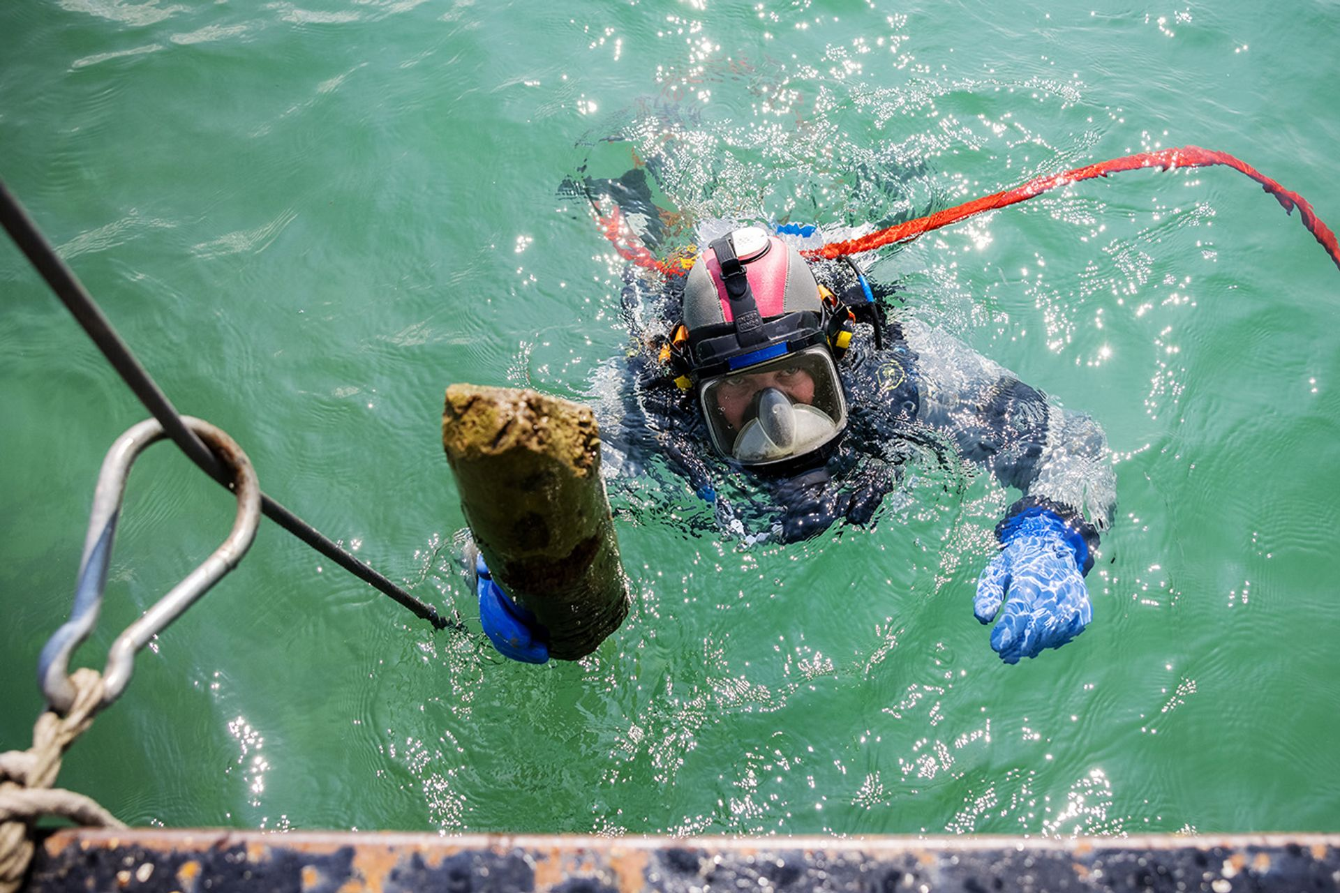 A diver emerging with a piece of wood retrieved from below the muddy bed of Lake Lucerne, where archaeologists have found the remains of houses that once stood on stilts. Philipp Schmidli