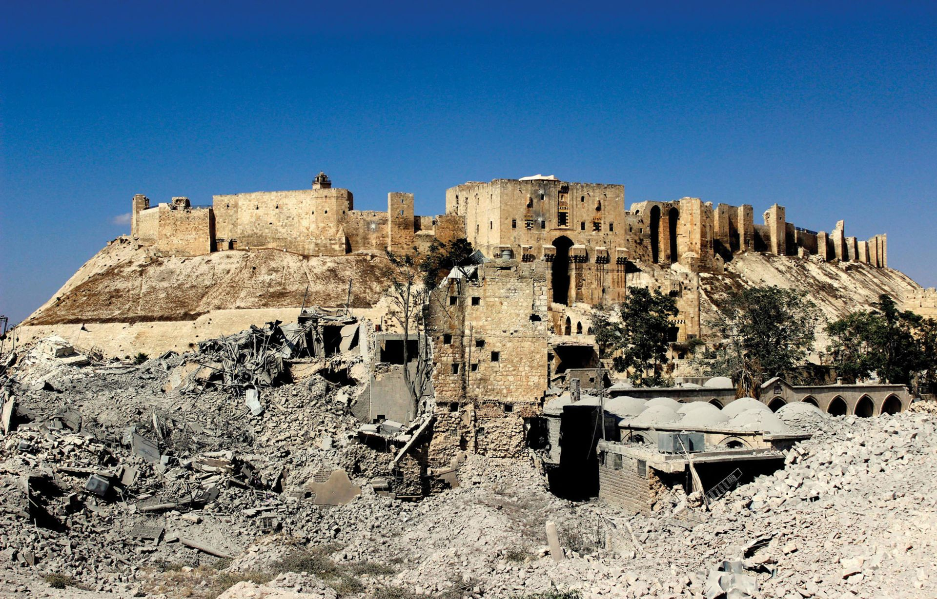 The entrace to the Citadel of Aleppo, with the ruins of the Khusruwiyah Mosque and the Carlton Hotel © Sultan Kitaz, 2014