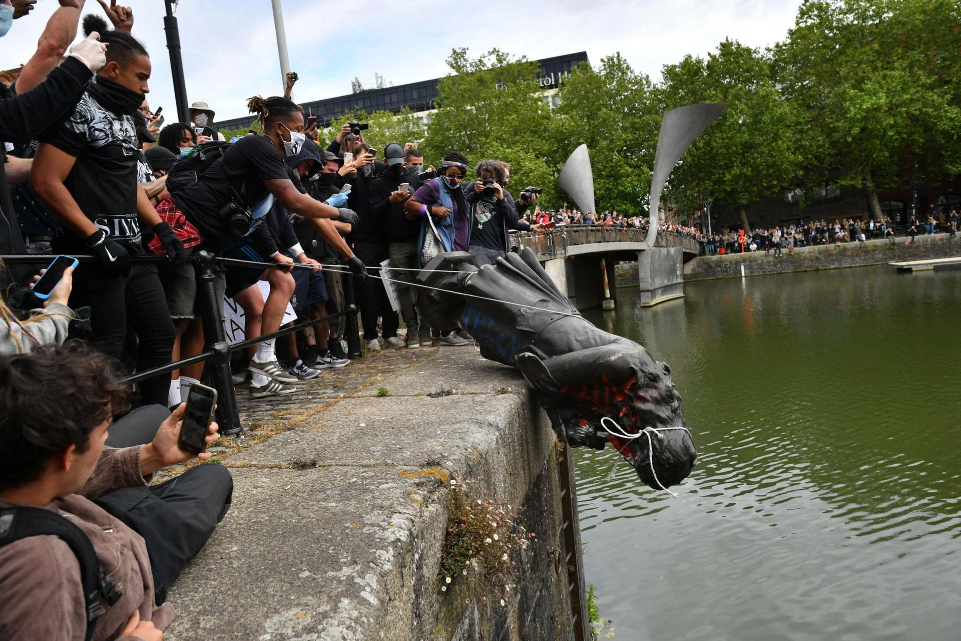 Protesters throw the statue of Edward Colston into Bristol harbour during a Black Lives Matter protest rally, in memory of George Floyd who was killed on 25 May while in police custody in the US city of Minneapolis © PA Images / Alamy Stock Photo