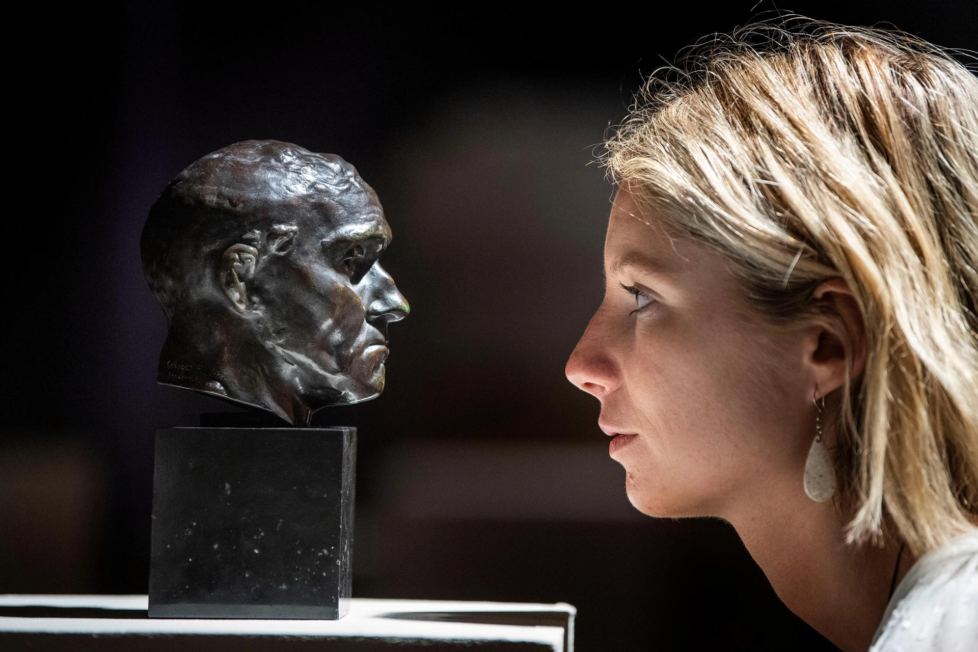 A member of Bonhams staff looks at a sculpture by Auguste Rodin before it is offered for sale. PA Images / Alamy Stock Photo