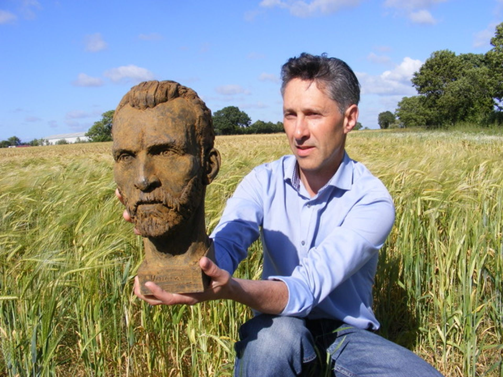 Anthony Padgett with his Van Gogh sculpture, photographed in a Lancashire wheatfield, 2018