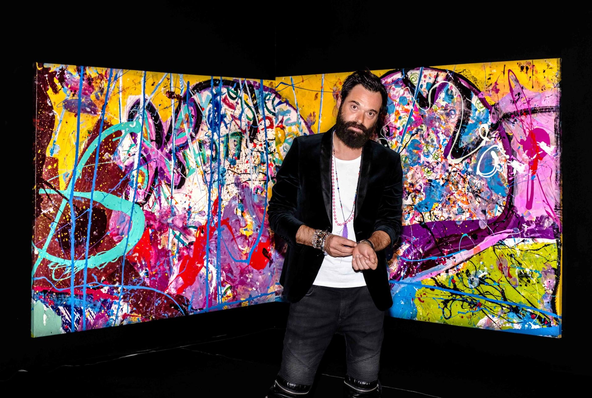Sacha Jafri in front of part of the painting Courtesy of Humanity Inspired