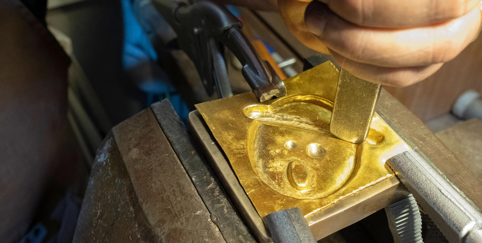 Nicolas Hugo hammers out a mould for a medallion