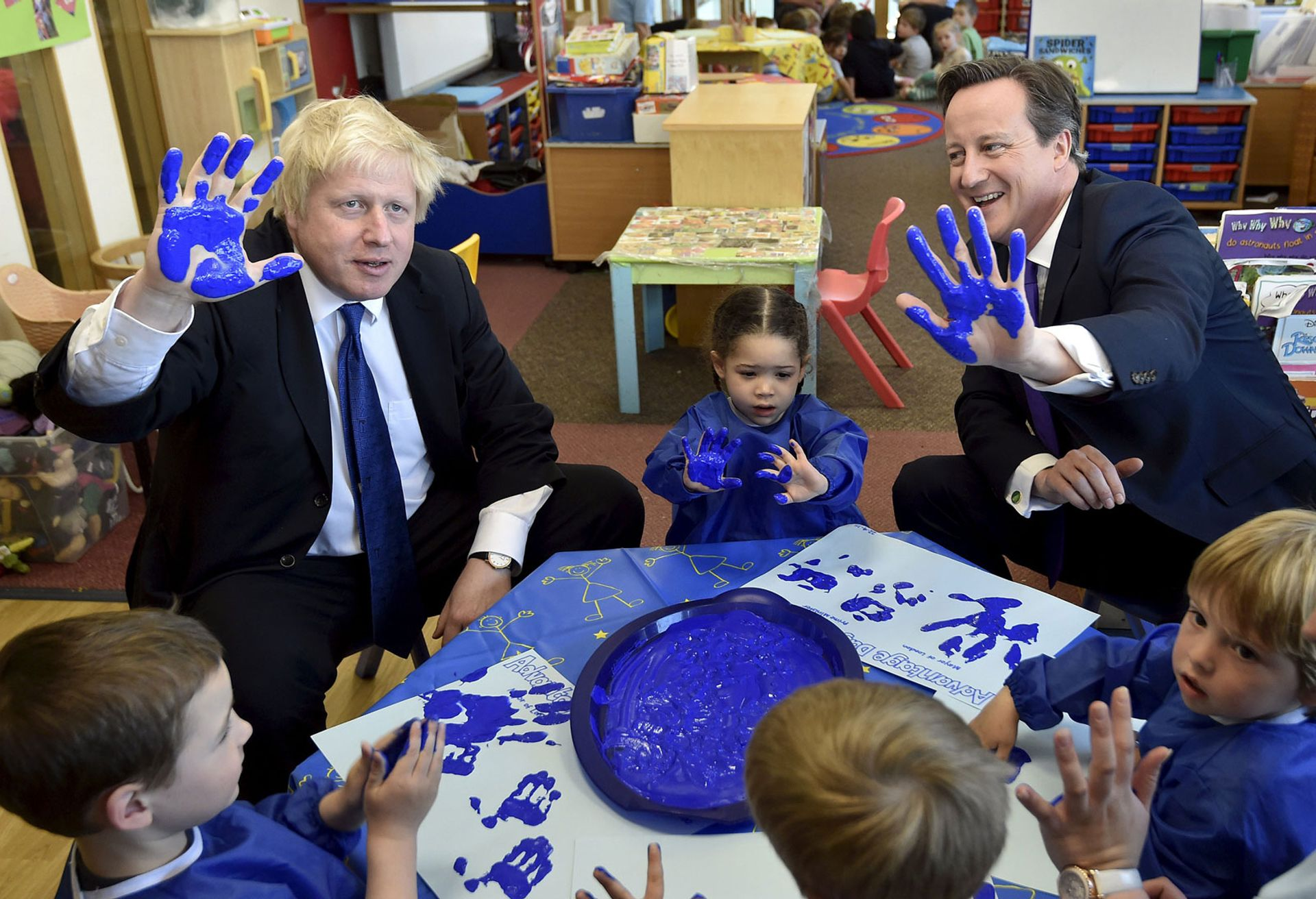 Boris Johnson in 2015 when he was Mayor of London with the UK's then prime minister David Cameron taking part in a hand-printing session with children Photo by Toby Melville - WPA Pool / Getty Images