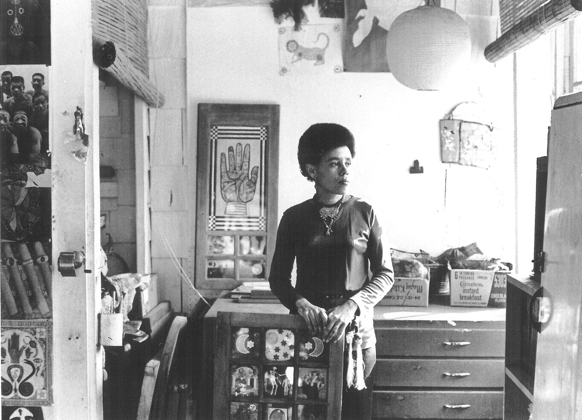 Betye Saar holding Black Girl's Window at her Laurel Canyon Studio, Los Angeles, California, 1970 Courtesy of the artist and Roberts Projects, Los Angeles, California, Photo Bob Nakamura. © 2019 Betye Saar, courtesy the artist and Robert Projects, Los Angeles