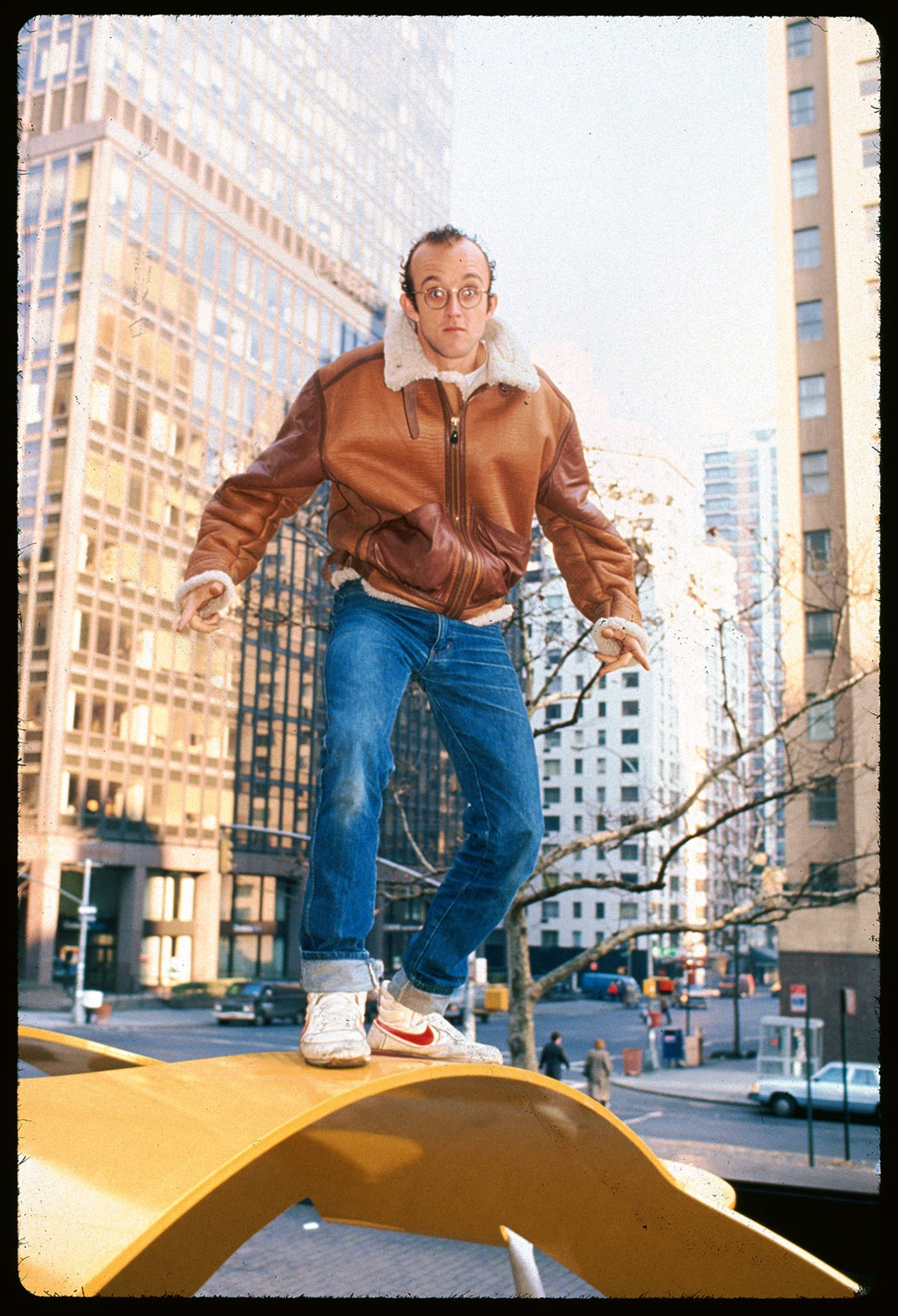 Keith Haring on top of one of his sculptures © Getty
