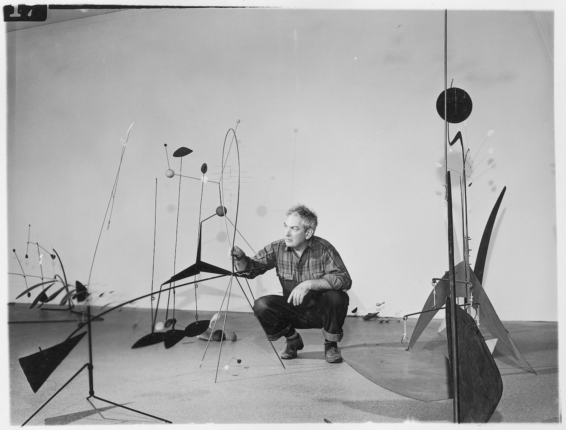 """Publicity photograph of Calder during the installation of """"Alexander Calder"""" in 1943 at the Museum of Modern Art Photographic Archive, The Museum of Modern Art Archives, New York. © 2021 Calder Foundation, New York / Artists Rights Society (ARS), New York"""