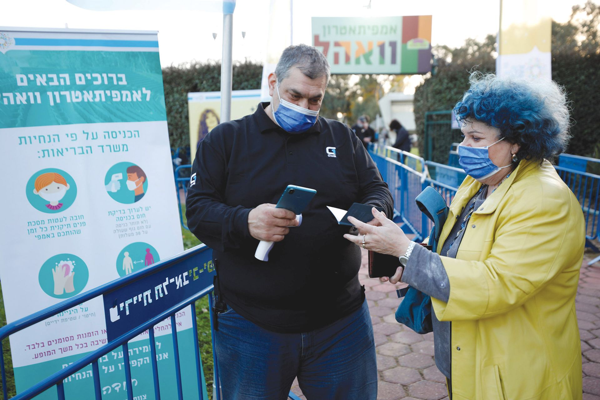 """A woman showing her """"green pass"""" as she enters singer Nurit Galron's concert in Yarkon Park, Tel Aviv, in late February Amir Cohen/Reuters/Alamy"""