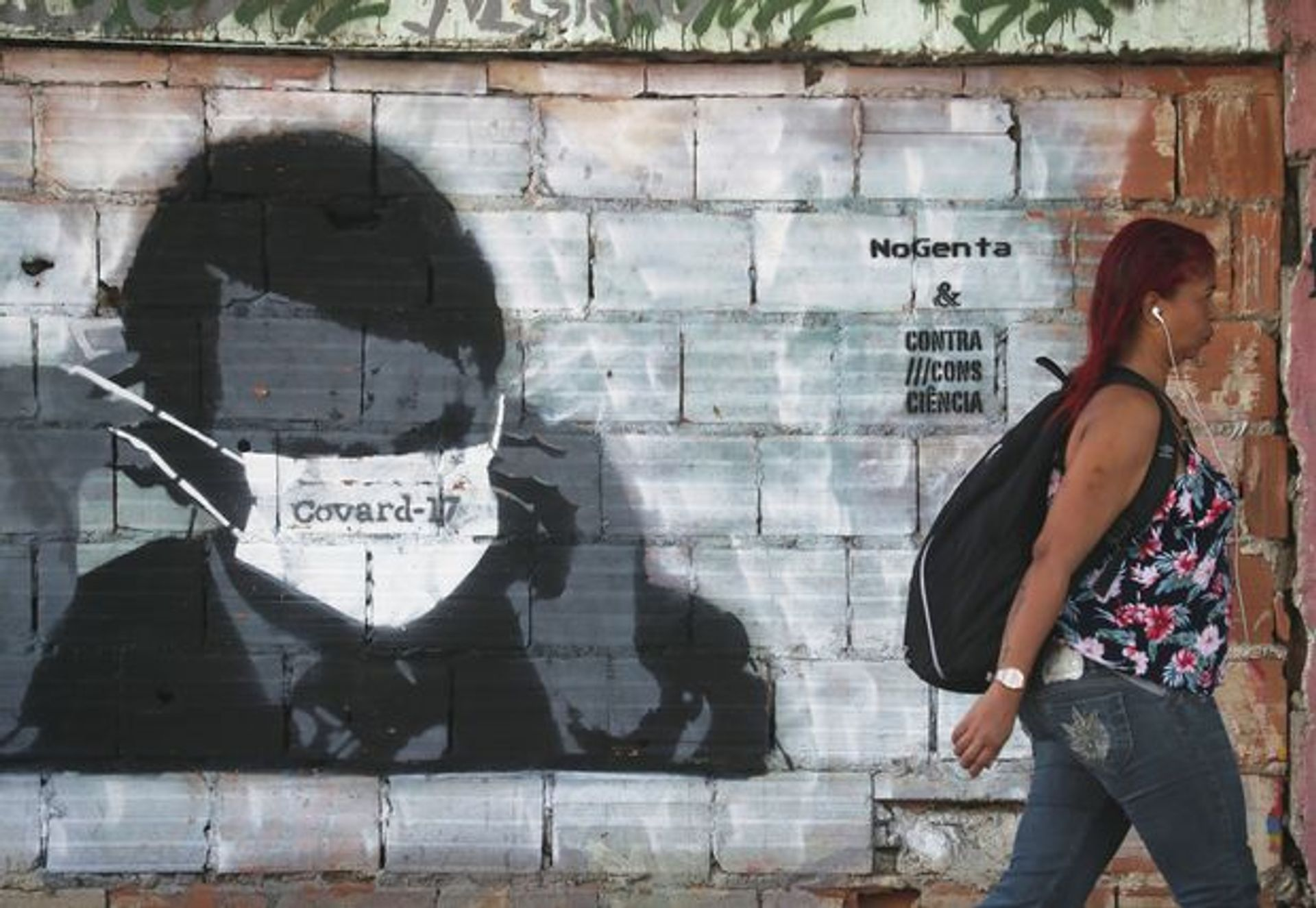 A woman walks past street art in Rio de Janeiro depicting Brazilian president Bolsonaro adjusting his protective face mask, marked 'Coward-17' in Portuguese. The number 17 is a reference to Bolsonaro's political party number. Sergio Moraes/Reuters