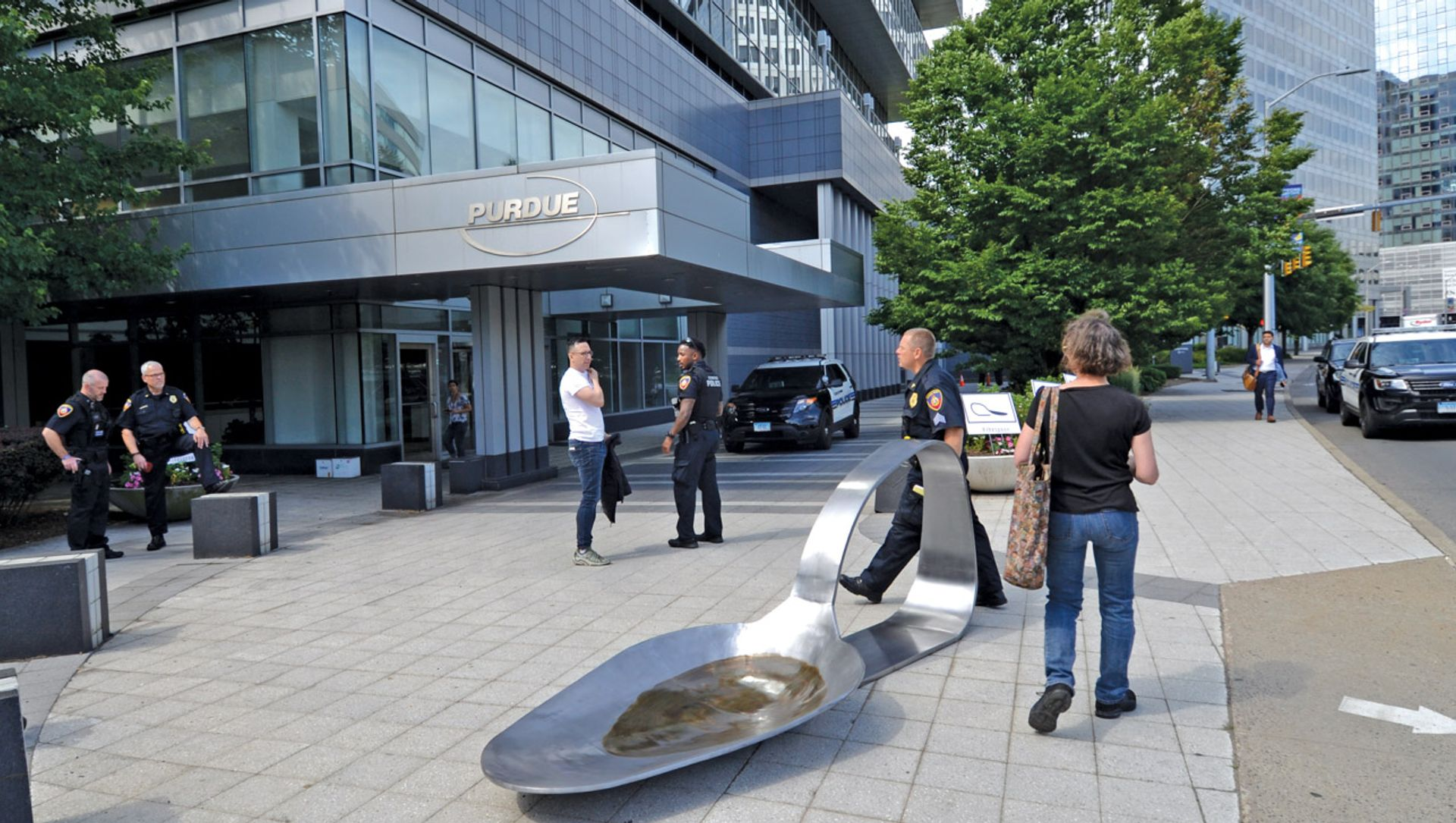 Domenic Esposito's opium-spoon sculpture was placed outside Purdue Pharma's offices by the gallery owner Fernando Luis Alvarez (in white shirt), who was later arrested for refusing to remove it Domenic Esposito
