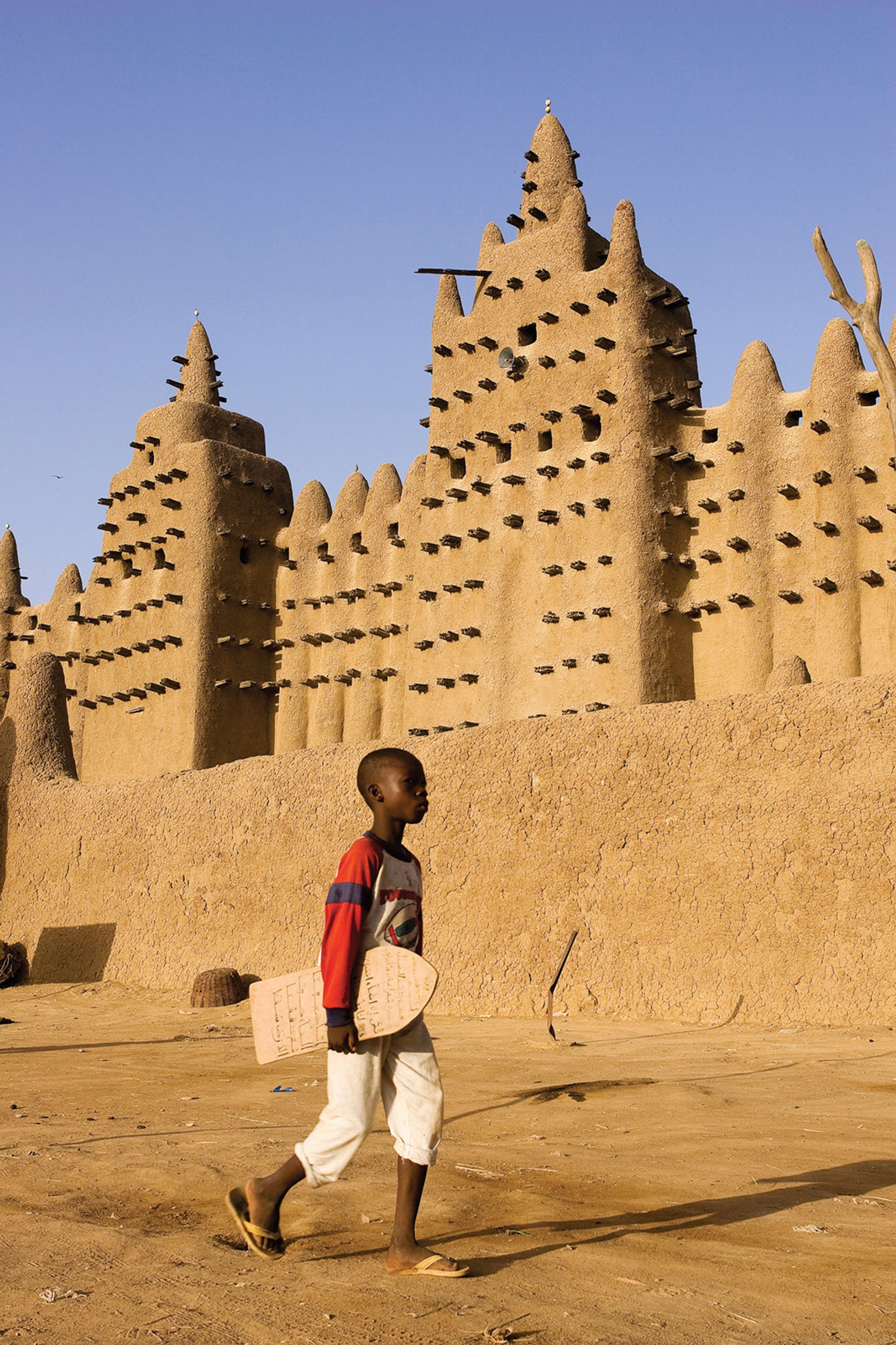 A boy carrying a lawh (wooden board on which he has written Qur'anic verses) walks past the Grand Mosque of Mopti, Mali Hemis/Alamy Stock Photo