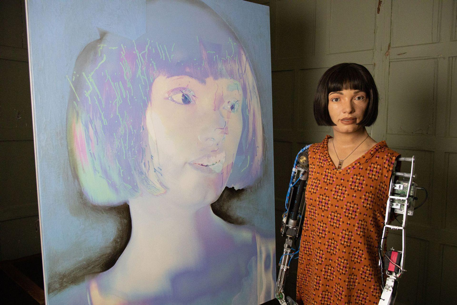 "Ai-Da alongside its—or should that be ""her""?—self portrait"