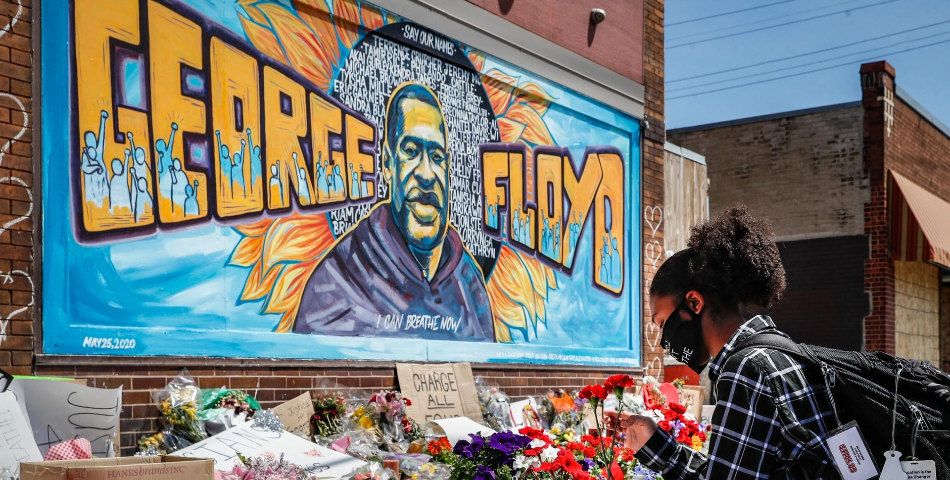 Malaysia Hammond, 19, places flowers at a memorial mural for George Floyd at the corner of Chicago Avenue and 38th Street, Sunday, May 31, 2020, in Minneapolis. Protests continued following the death of George Floyd, who died after being restrained by Minneapolis police officers on Memorial Day AP Photo/John Minchillo