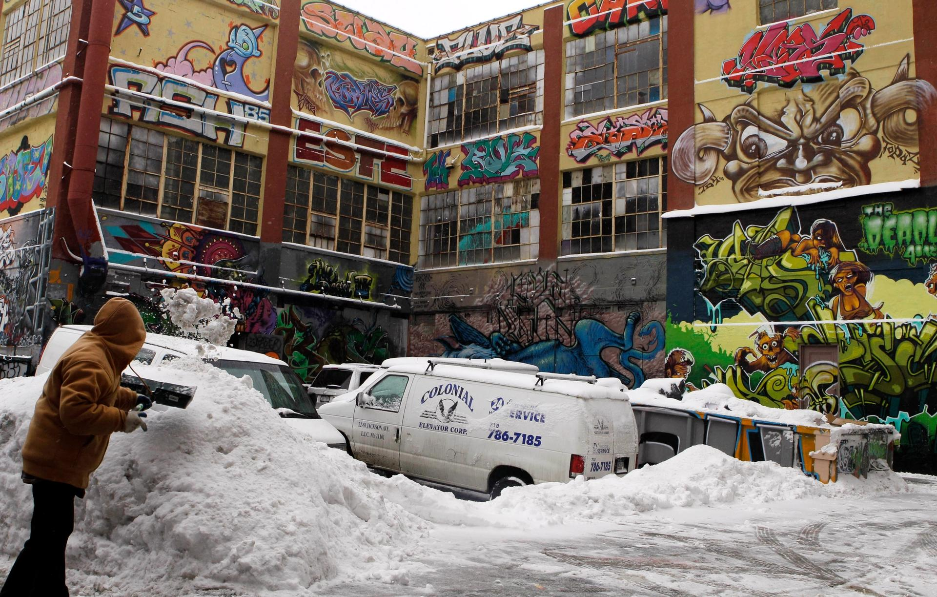 A man shovels snow to clear a driveway near the 5pointz street art complex before it was demolished AP Photo/Frank Franklin II