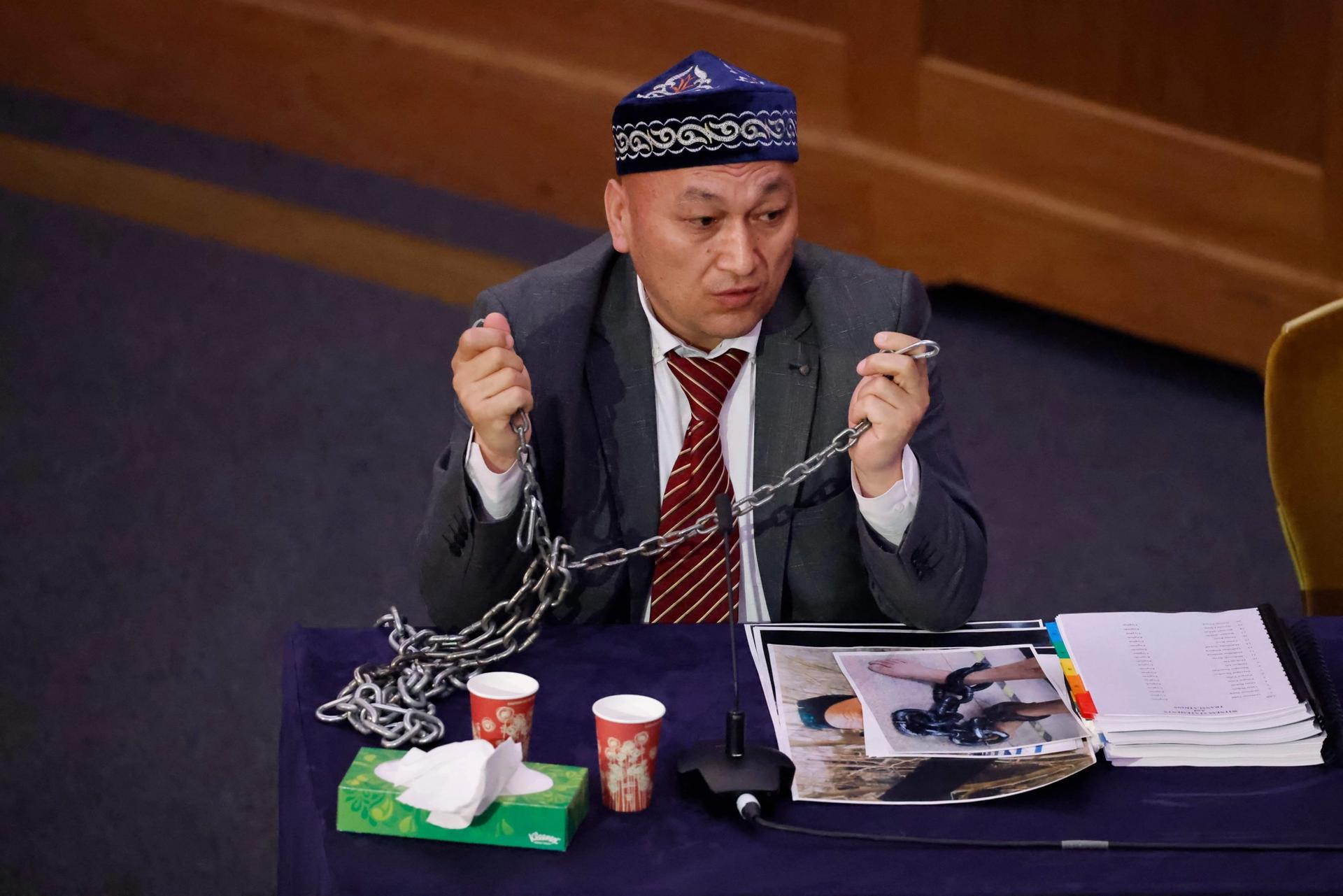 Kazakh-Uyghur witness Omir Bekali demonstrates how he was shackled in chains at a detention camp in Xinjiang as he speaks on the first day of hearings at the Uyghur Tribunal Photo: Tolga Akmen / AFP via Getty Images