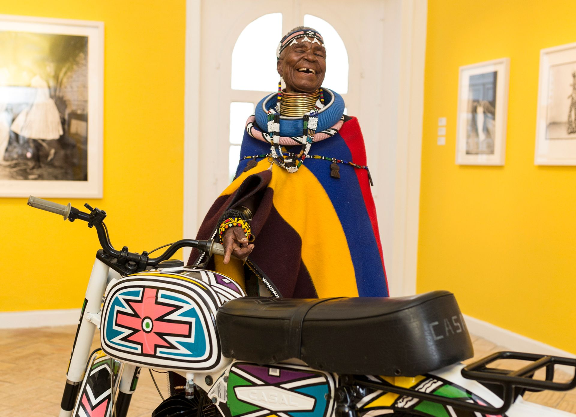 Esther Mahlangu with the motorbike she has decorated for the exhibition African Passions, part of the inaugural Evora Africa festival in the Alentejo region of Portugal African Passions, Palacio Cadaval, 2018