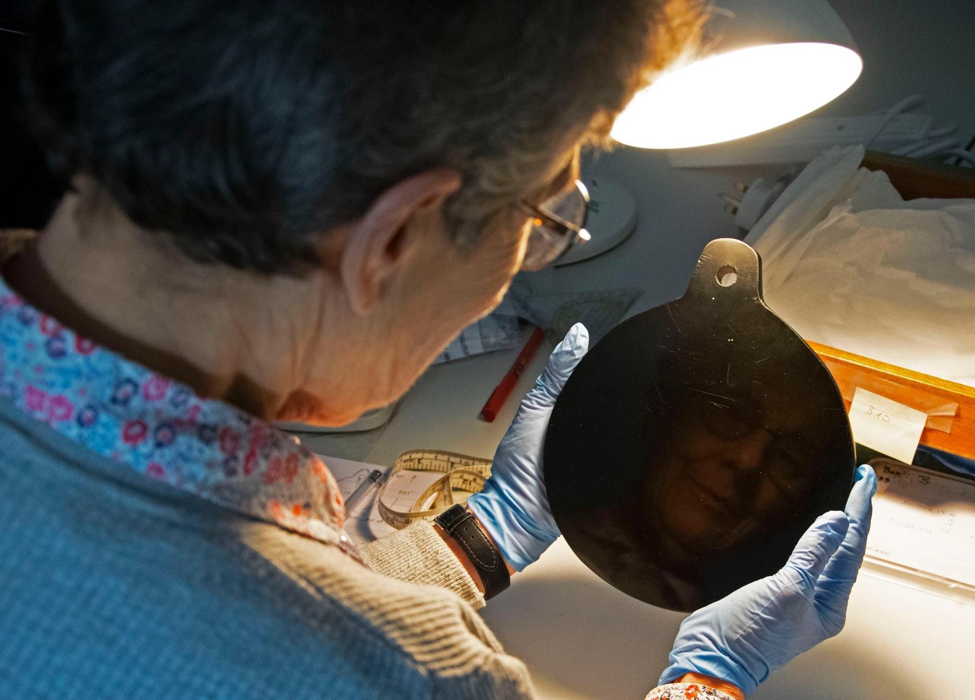 Researcher Elizabeth Healey studying John Dee's obsidian spirit mirror.  © S. Campbell