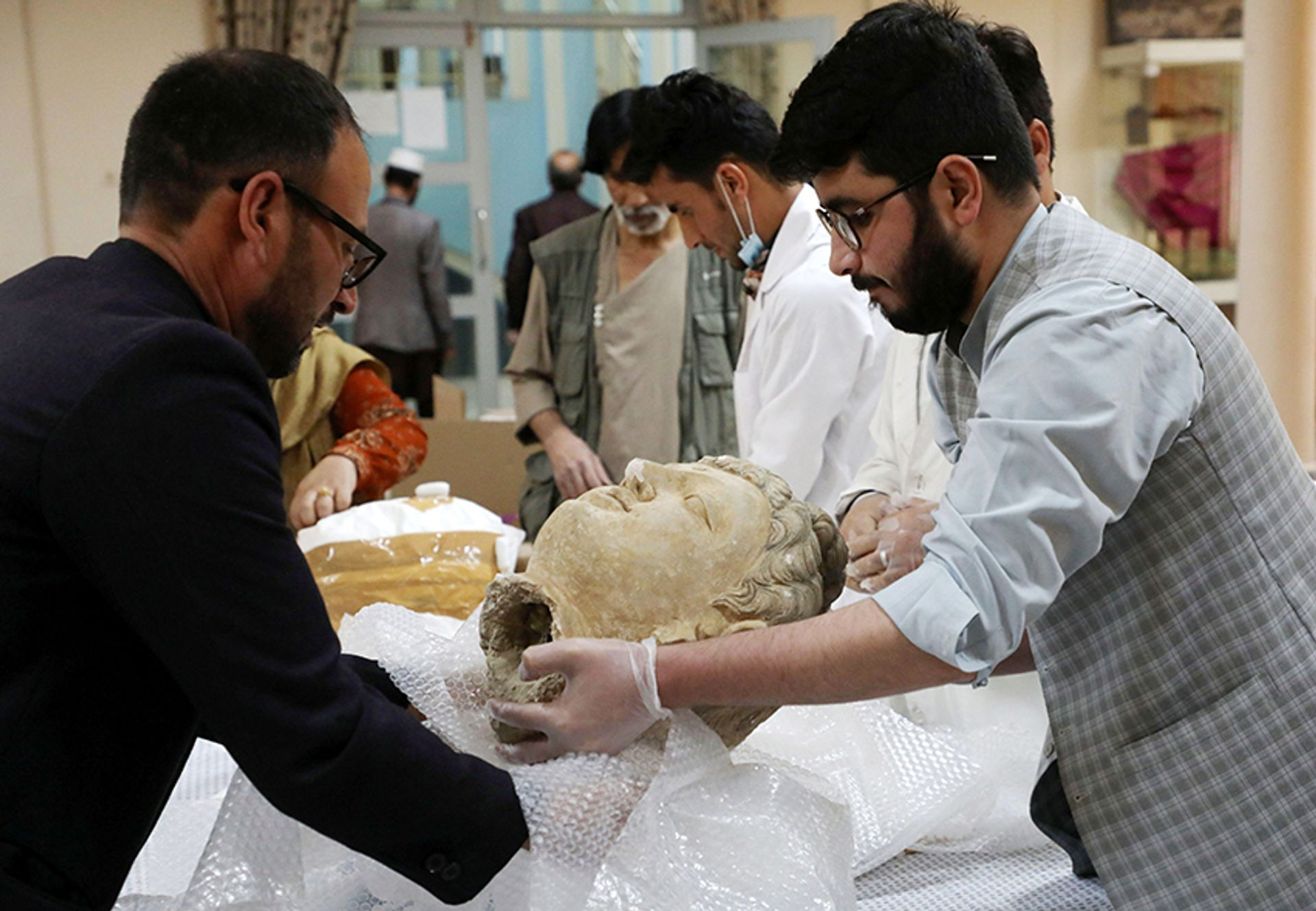Museum workers unpack an artefact that was smuggled to the US during the wars and was only just returned to the Afghan National Museum in Kabul, Afghanistan, on 29 April 2021 © Reuters / Alamy Stock Photo