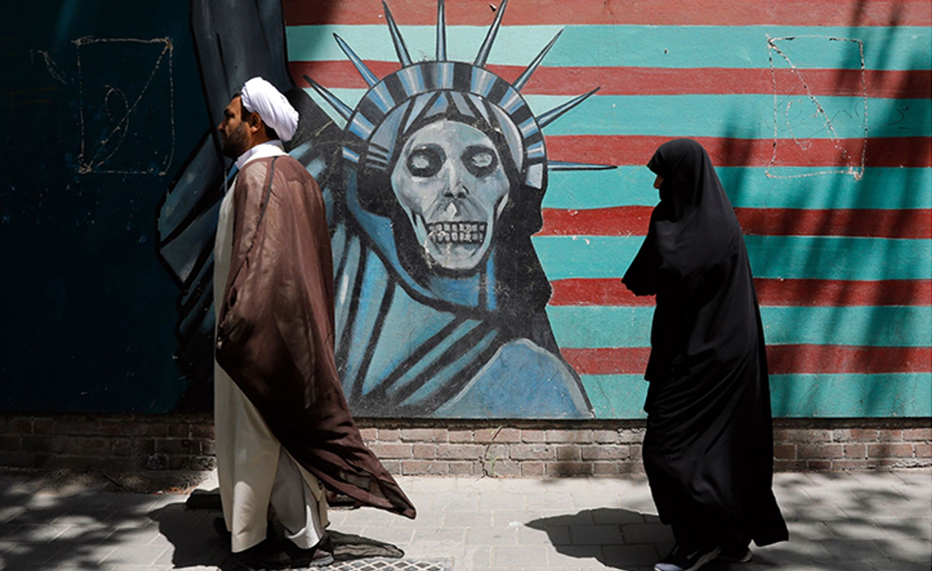 An Iranian cleric and woman walk past an anti-US mural  during an anti-US and Israeli protest outside the former US embassy in Tehran on 16 May 2018 Abedin Tahrkenareh/EPA-EFE/REX/Shutterstock