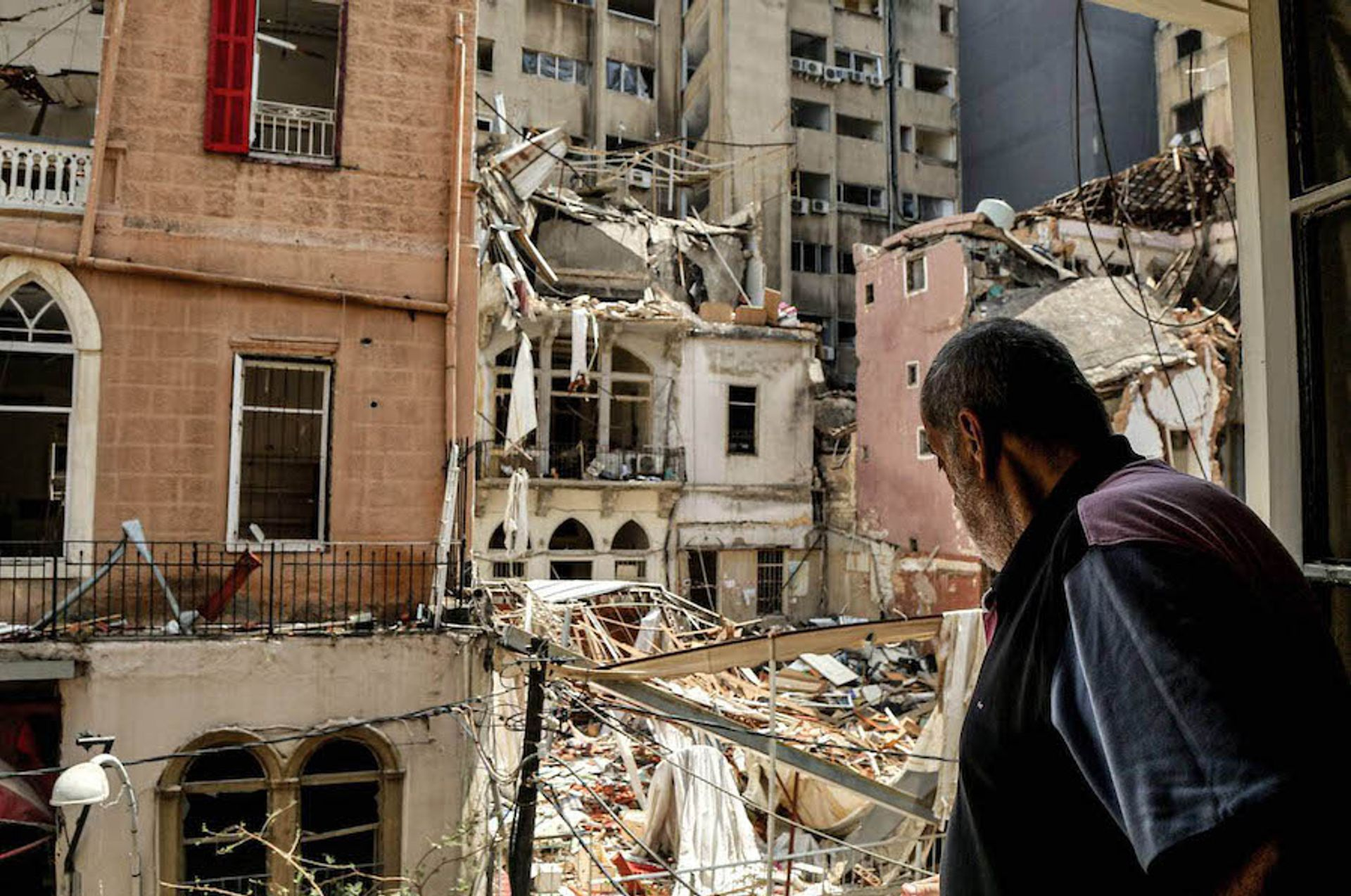 A man stares from a window towards the ruins of a heritage building in the Mar Mikhael neighbourhood, one of several historic districts in Beirut that bore the brunt of the explosion Marwan Naamani/dpa/Alamy Live News
