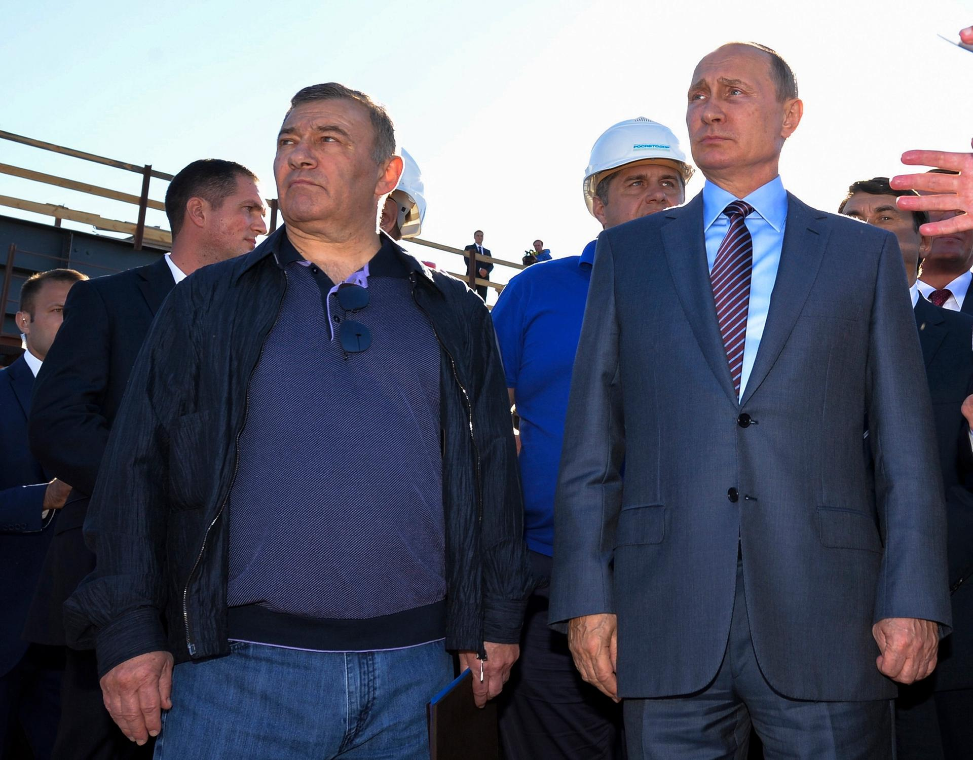 Russian President Vladimir Putin joins billionaire Arkady Rotenberg (left), during to a visit to the construction site of the Kerch Strait bridge in Kerch, Crimea. Investigators traced $18m in art purchases to shell companies linked to Rotenberg and his brother Boris, who are close Putin associates who American officials say benefited financially from the annexation of Crimea Alexei Druzhinin/Sputnik, Kremlin, File Pool Photo via AP