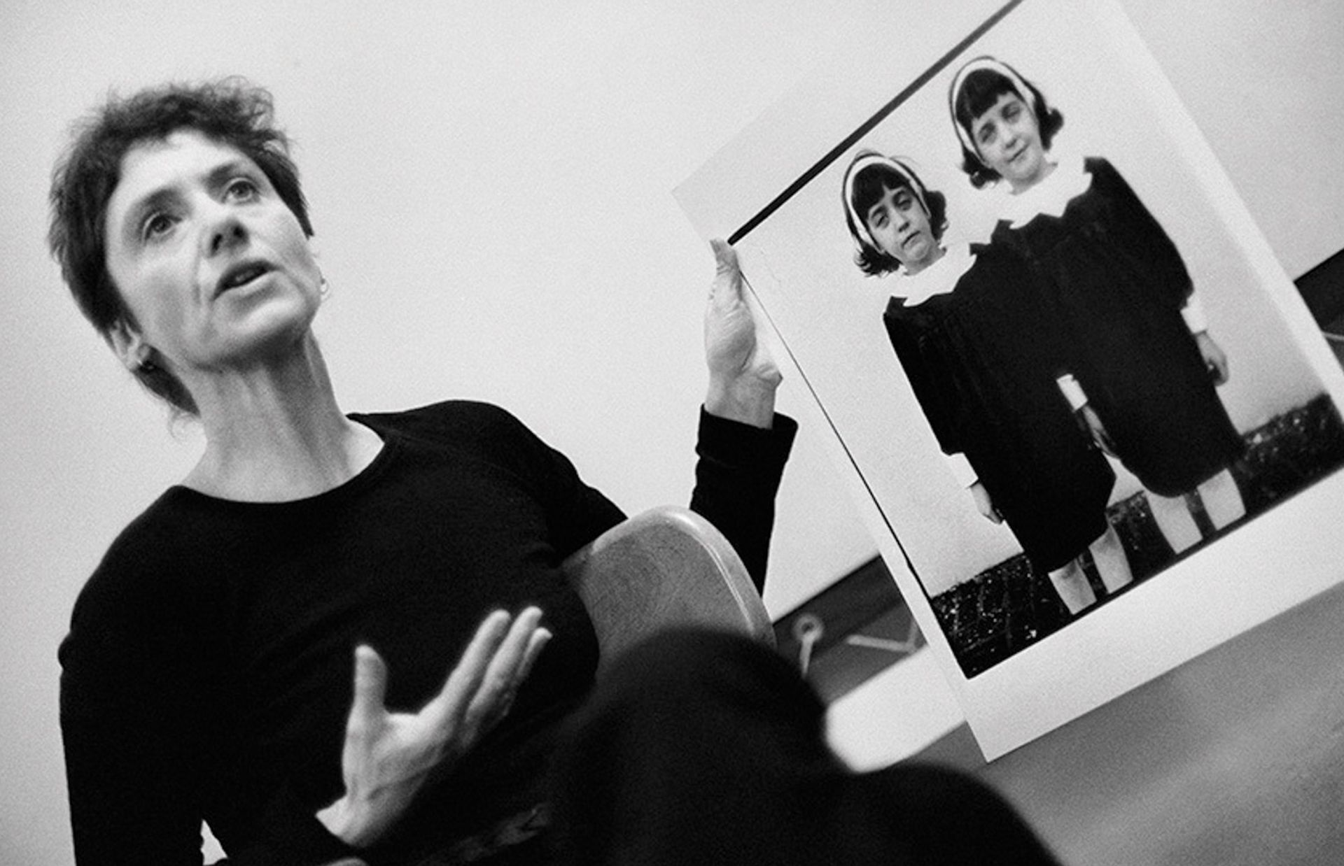 Photographer Diane Arbus, pictured here in 1970, holding up one of her most famous photographs, Identical Twins, Roselle, New Jersey (1966), during a lecture at the Rhode Island School of Design © Stephen A Frank.