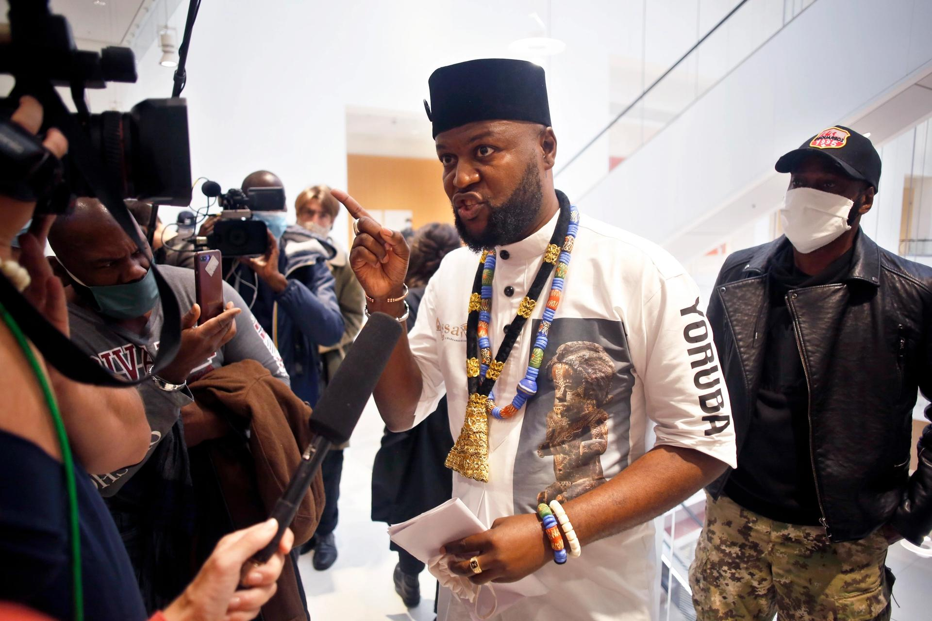 The Congolese activist Emery Mwazulu Diyabanza speaks to the media at the Palais de Justice courthouse, in Paris, where he and others are on trial on aggravated theft charges for trying to remove a 19th century African funeral pole from a Paris museum, in a protest against colonial-era plundering of African art © AP Photo/Thibault Camus