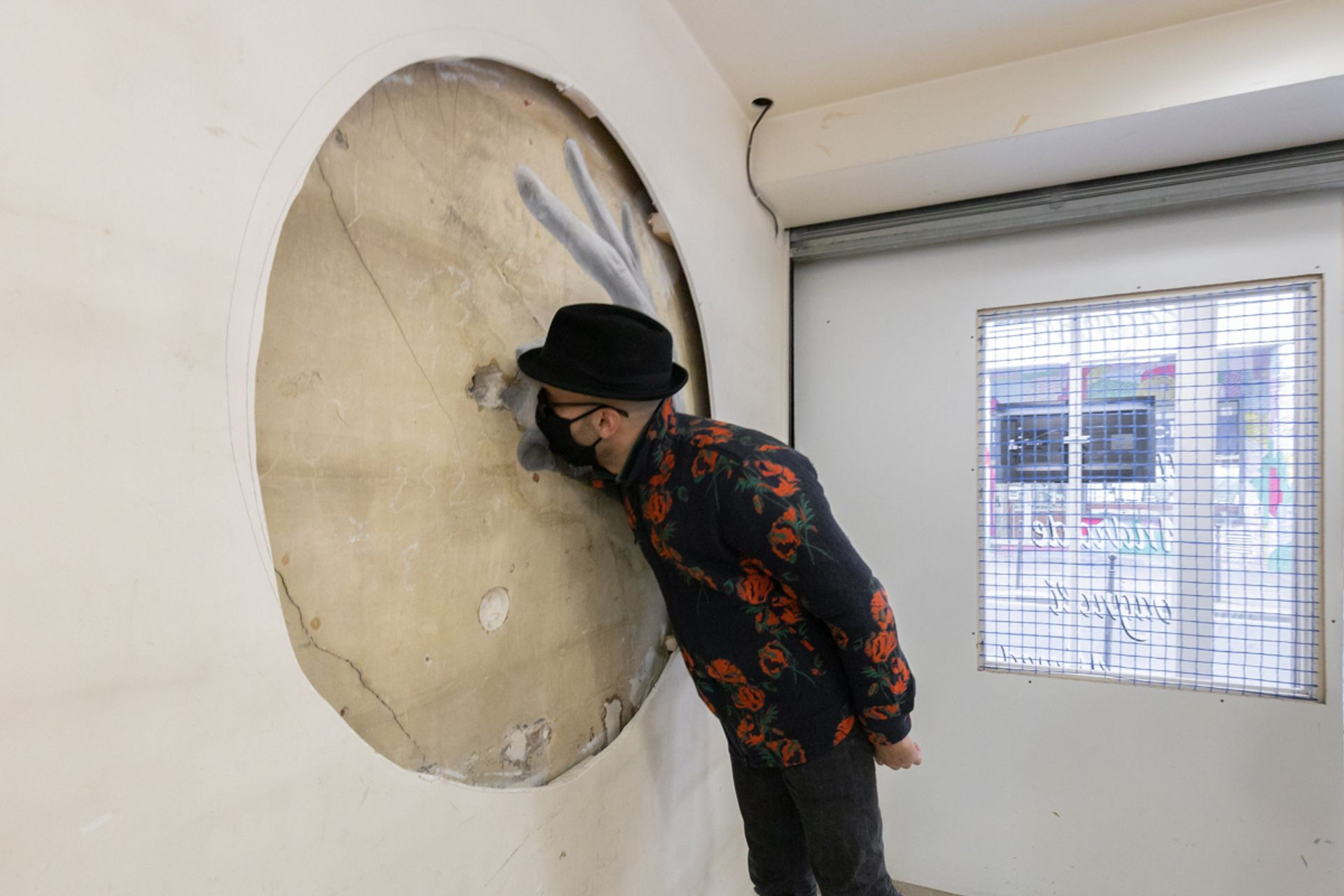 """JR inspects a work in his exhibition """"Truc a faire"""" at Galleria Continua Paris Photo: © Sara De Santis. Courtesy of the artists and Galleria Continua"""