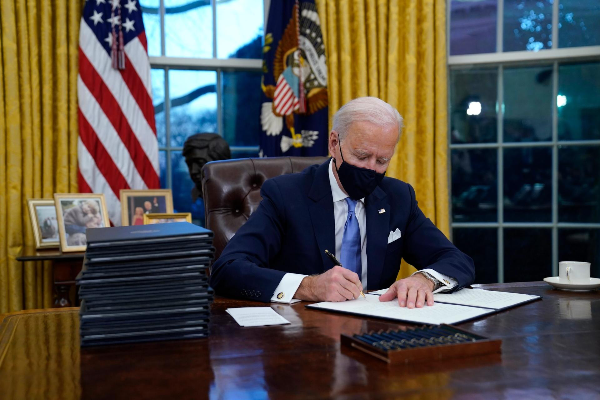 President Joe Biden signs his first executive order in the Oval Office of the White House on 20 January AP Photo/Evan Vucci