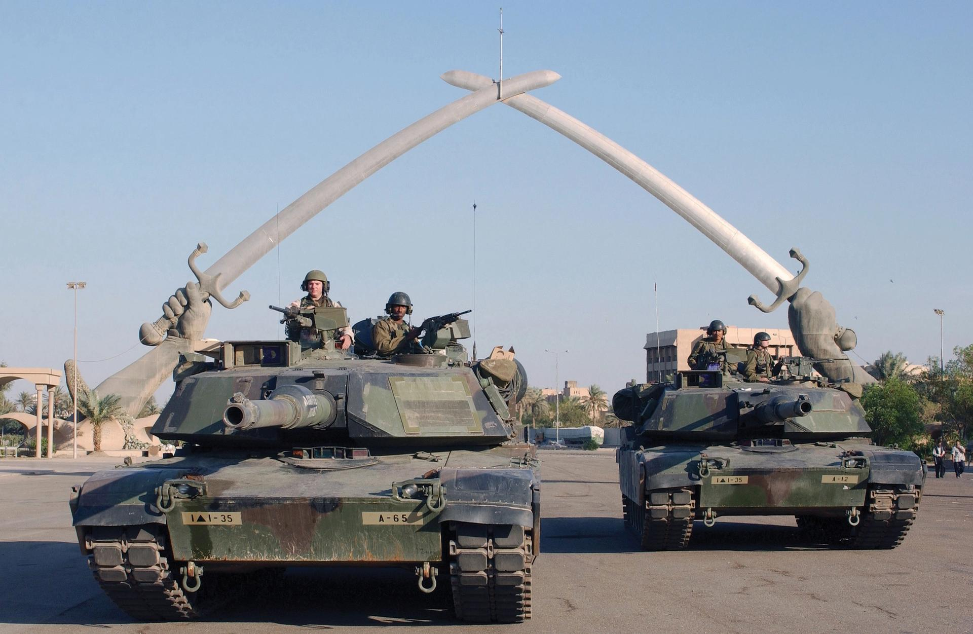"""US Army tanks and soldiers stop under the """"Hands of Victory"""" in Ceremony Square, Baghdad, during Operation Iraqi Freedom, 13 November 2003 Photo: Technical Sergeant John L. Houghton, Jr, United States Air Force"""