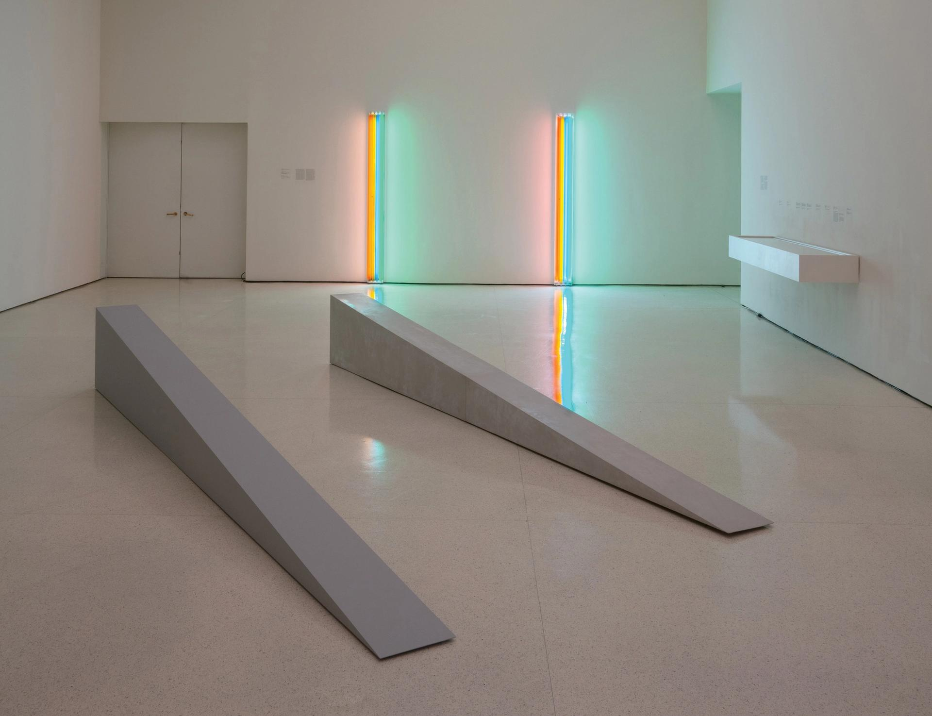 In foreground, two fabrications of Robert Morris's Untitled (Door Stop), 1965. (On left: 2018 artist-supervised, museum-made plywood fabrication; on right: 1965 fiberglass fabrication).  On far wall: two fabrications of Dan Flavin's Untitled (to Henri Matisse) 1964. (On left: historical fabrication received from Panza; right: 1995 fabrication produced in coordination with the Flavin studio) David Heald/© Solomon R. Guggenheim Foundation, New York