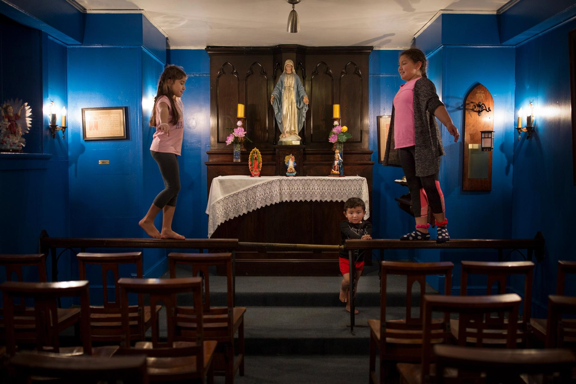 """On the left, Dulce Carvajal swinging with her feet up the sanctuary rail of the Chapel of Holyrood Church in Manhattan, New York, in September 2017, with her sister Dulce and her brother David. """"I like this church, but I miss my house, there we have a big yard with chickens and in the summer my mom sets a plastic pool up for us,"""" Dulce says. Cinthya Santos Briones"""