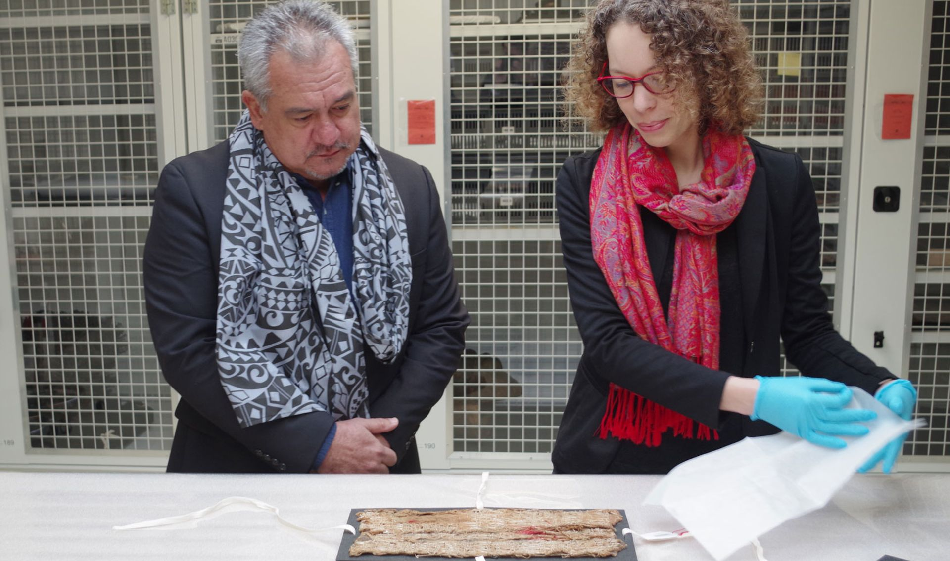 Stéphanie Leclerc-Caffarel, head of Oceanic Collections at the Musée du Quai Branly–Jacques Chirac, presents the fragment of maro 'ura to Heremoana Maamaatuiahutapu, the culture minister of French Polynesia © Gaëtan Deso