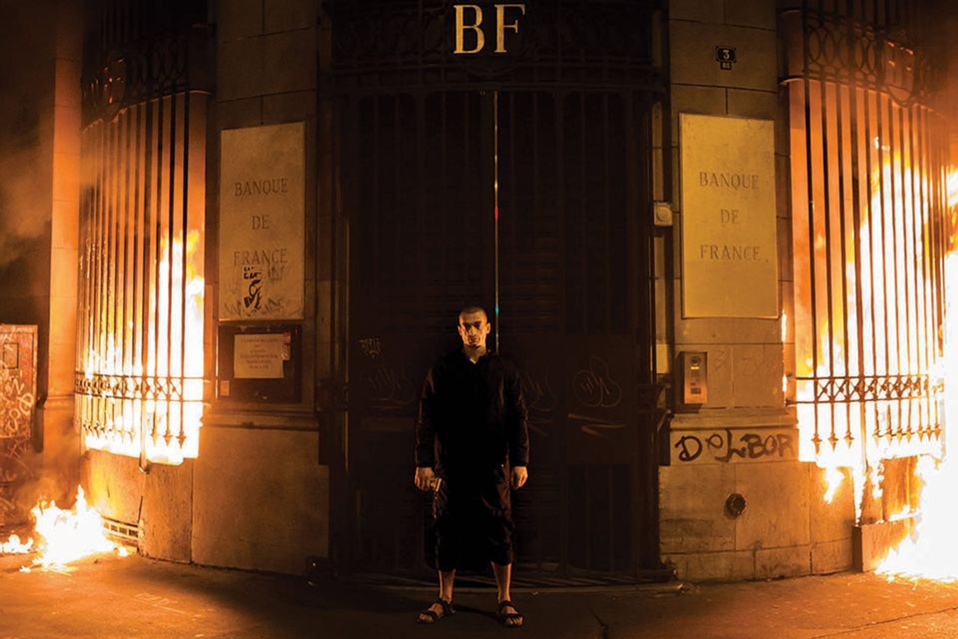 Pyotr Pavlensky poses in front of a Bank of France building after setting fire to the window gates as part of a performance in Paris ©  AP Photo/Capucine Henry