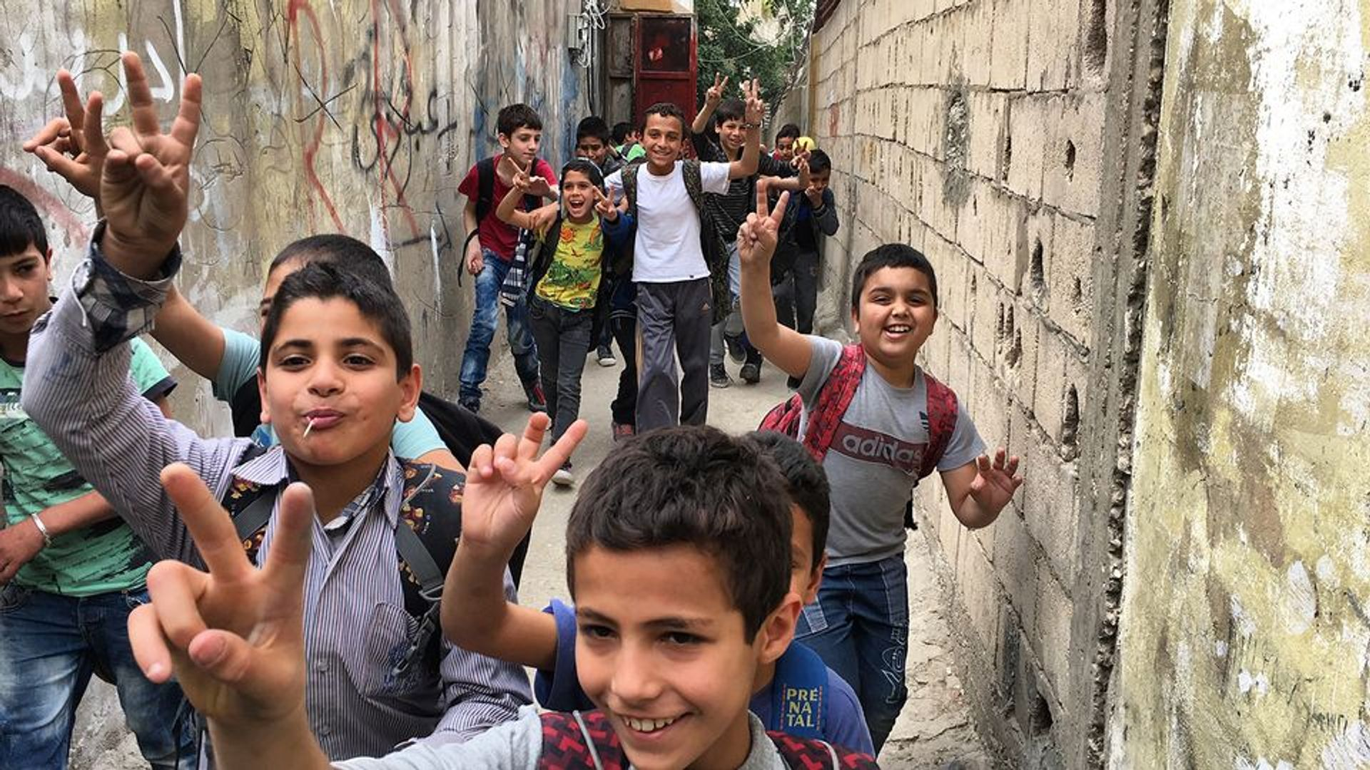 A group of children run through Ain al-Hilweh, the largest Palestinian refugee camp in Lebanon, from Human Flow by Ai Weiwei © Photo courtesy of Amazon Studios