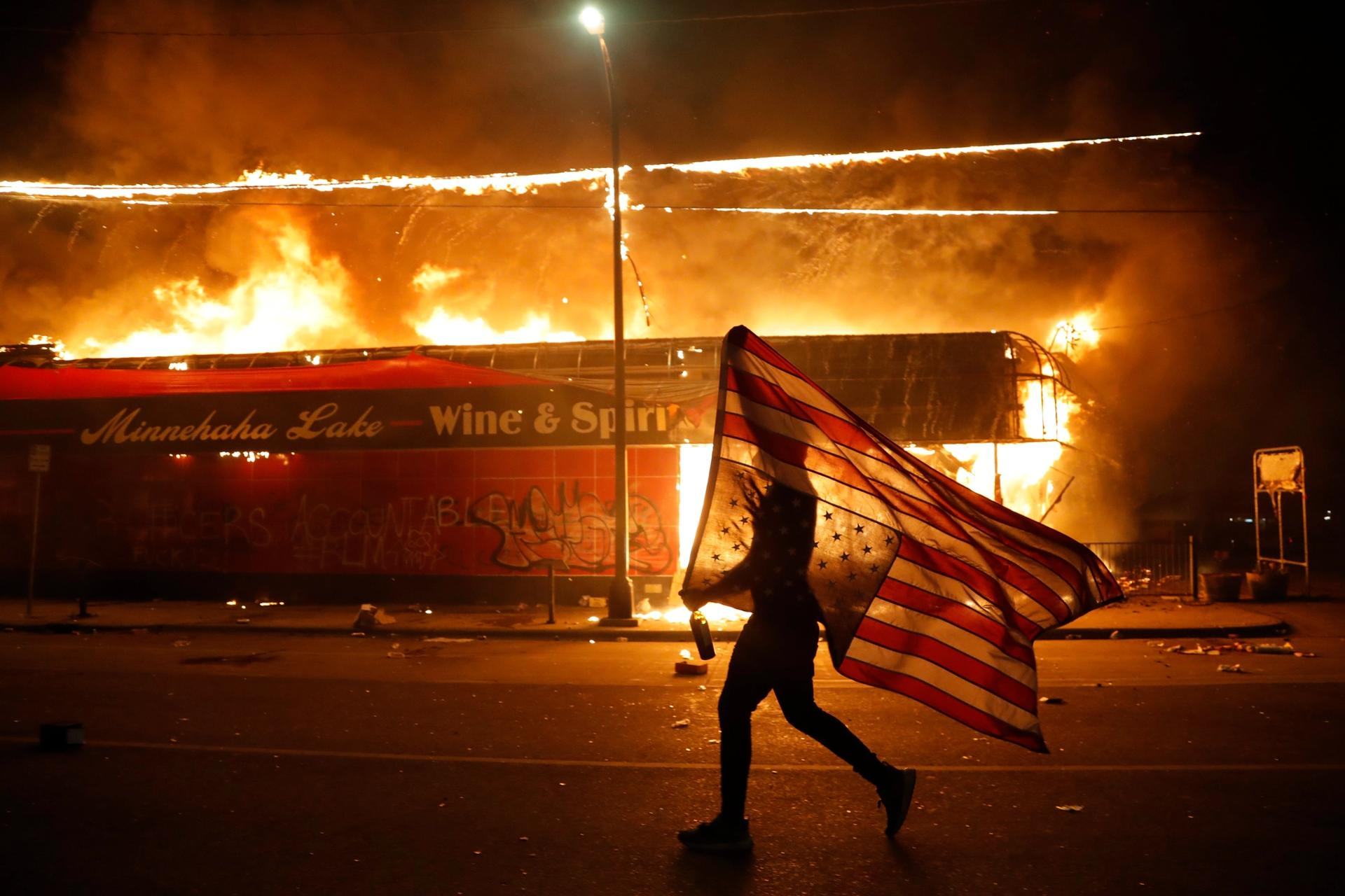 A protester carries a US flag upside down, a sign of distress, next to a burning building Thursday, 28 May 2020, in Minneapolis. Protests over the death of George Floyd, a black man who died in police custody Monday, broke out in Minneapolis for a third straight night AP Photo/Julio Cortez