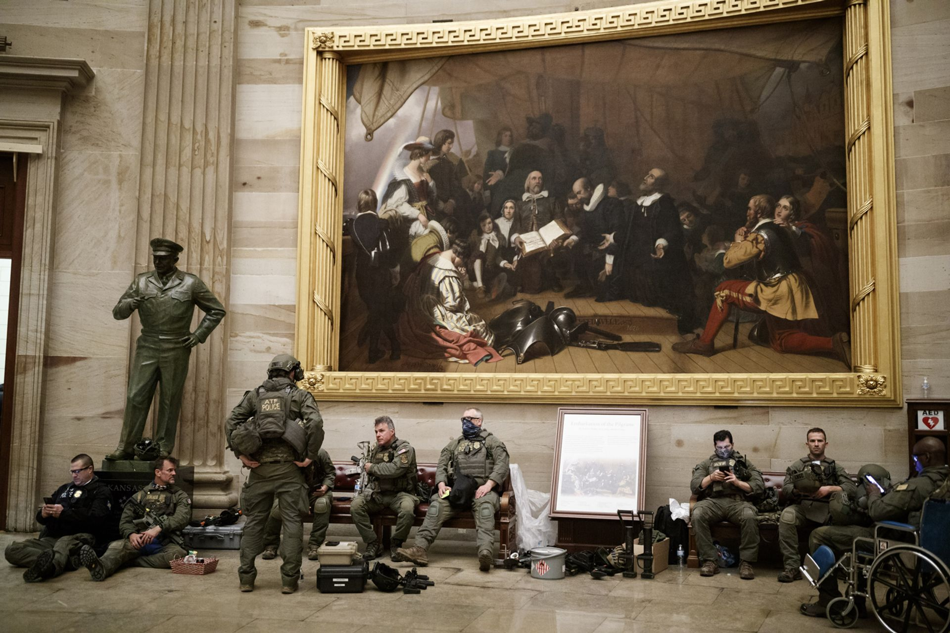 Members of law enforcement rest beneath Robert Walter Weir's painting Embarkation of the Pilgrims (around 1837) in the rotunda of the US Capitol in Washington, DC. Photo: Ting Shen/Bloomberg via Getty Images