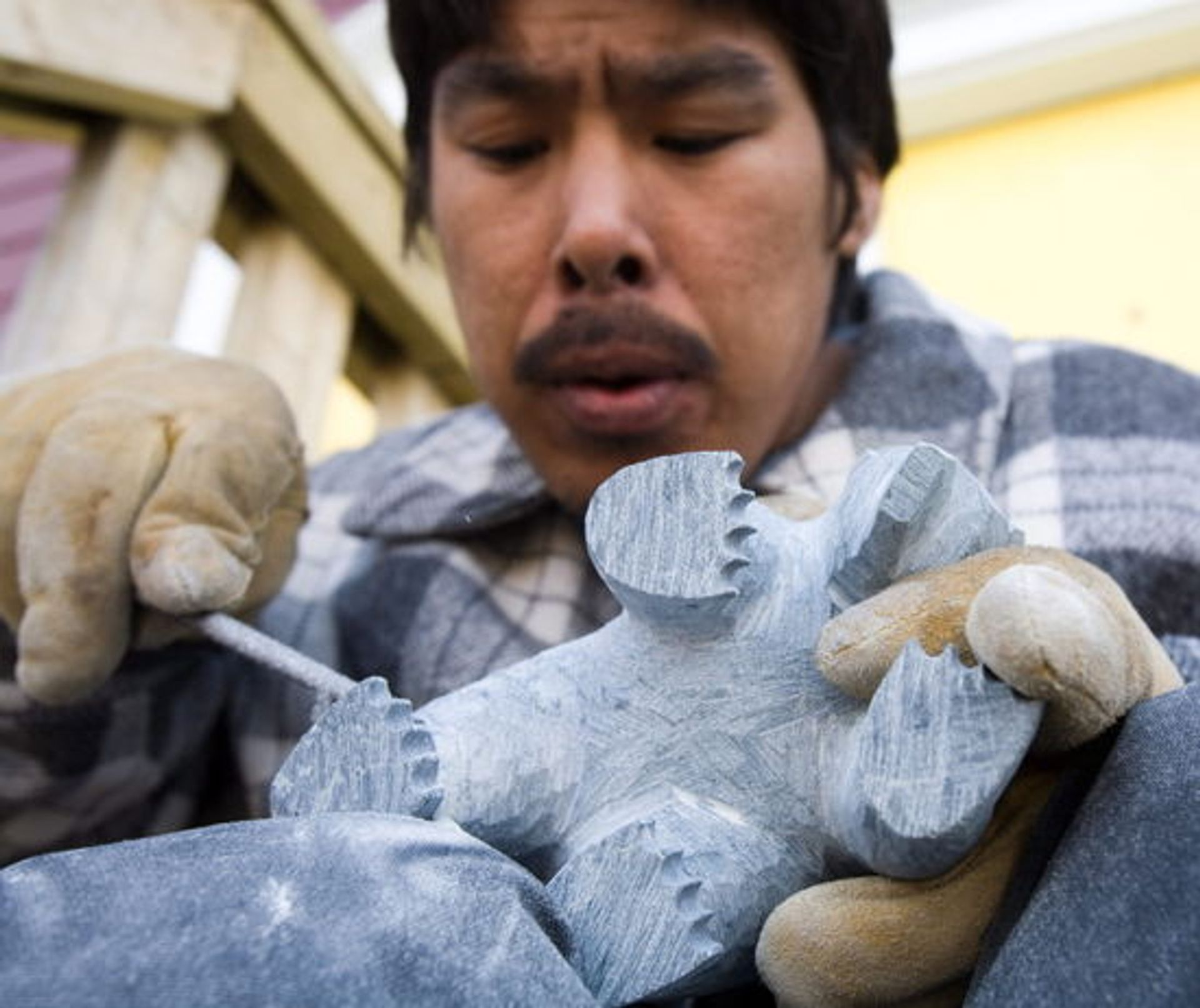 Inuit stone carver Ali Riaq of Cape Dorset works on a polar bear in Iqaluit, Nunavut. Canadian Press/Shutterstock