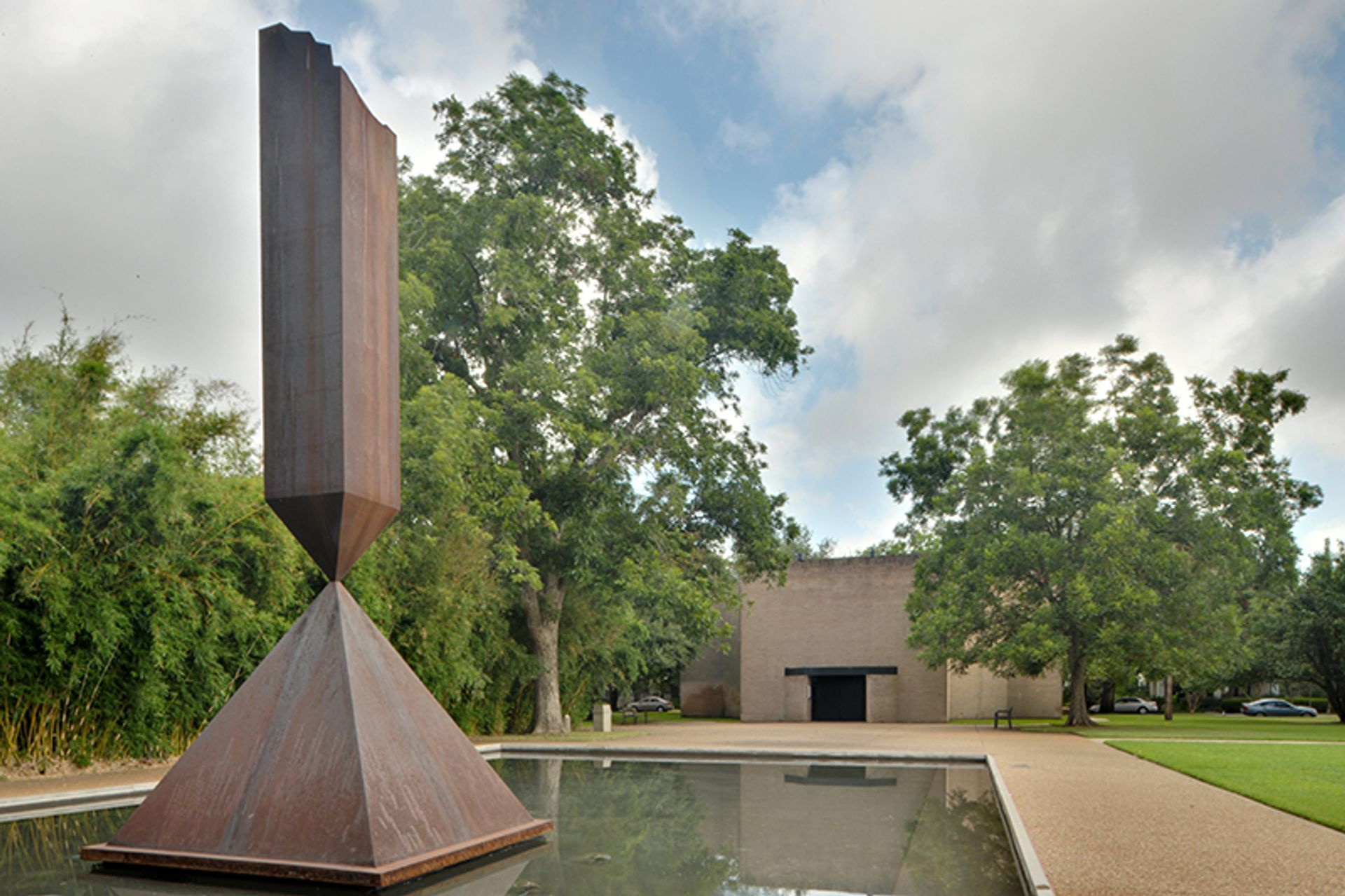 Broken Obelisk (1969) by Barnett Newman in the reflecting pool on the grounds of Rothko Chapel in Houston, Texas Wikimedia Commons