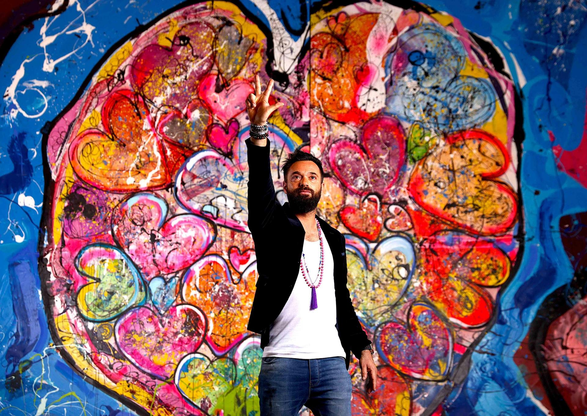 Sacha Jafri in front of the painting that contains Will Smith's handprints, titled The Journey of Humanity—With Love we are Reconnected, Inspired, Re-Energized Courtesy of Sacha Jafri
