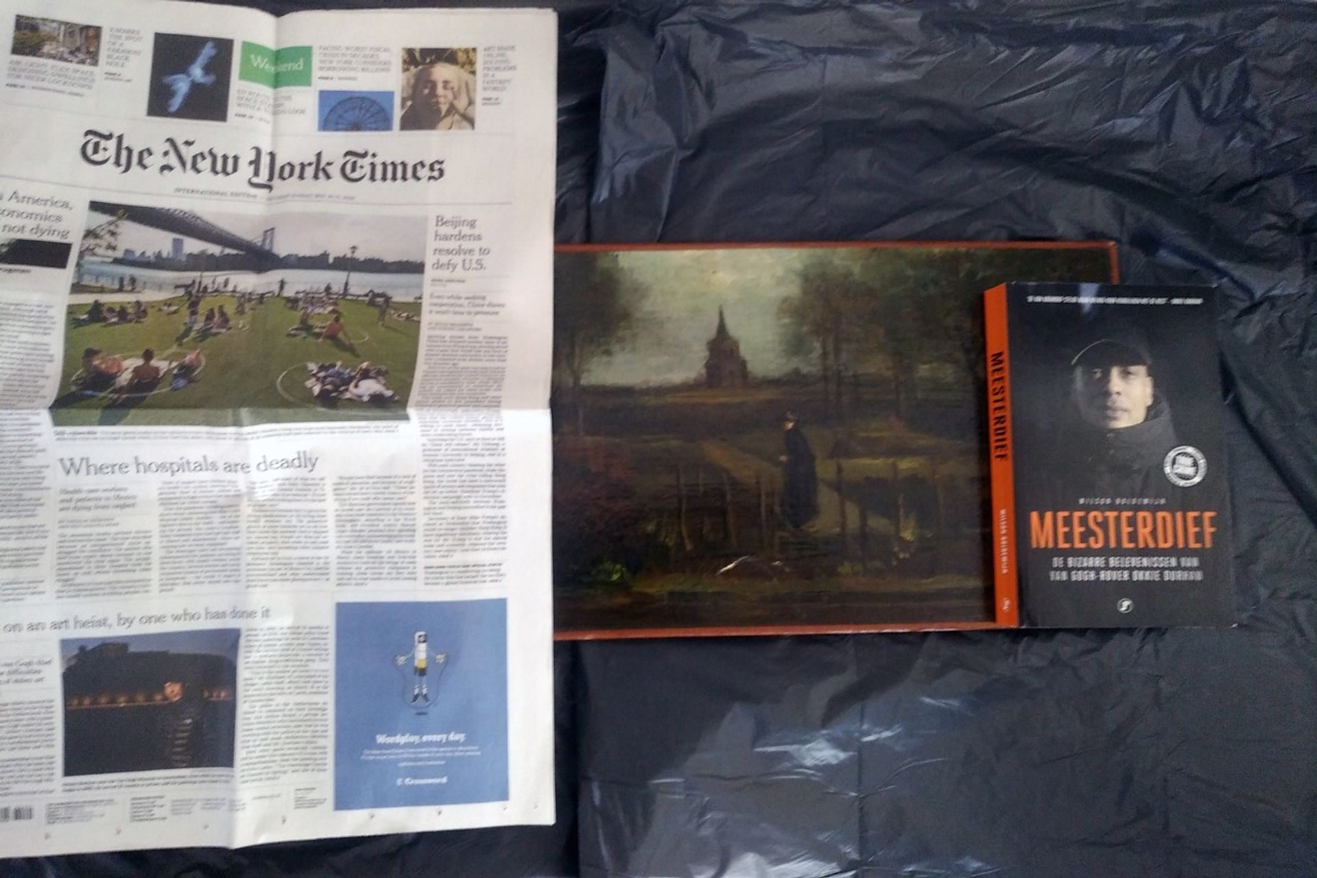 Van Gogh's The Parsonage Garden at Nuenen in the Spring (1884) with a copy of the New York Times (30 May 2020) and Wilson Boldewijn's book Meesterdief (2018)
