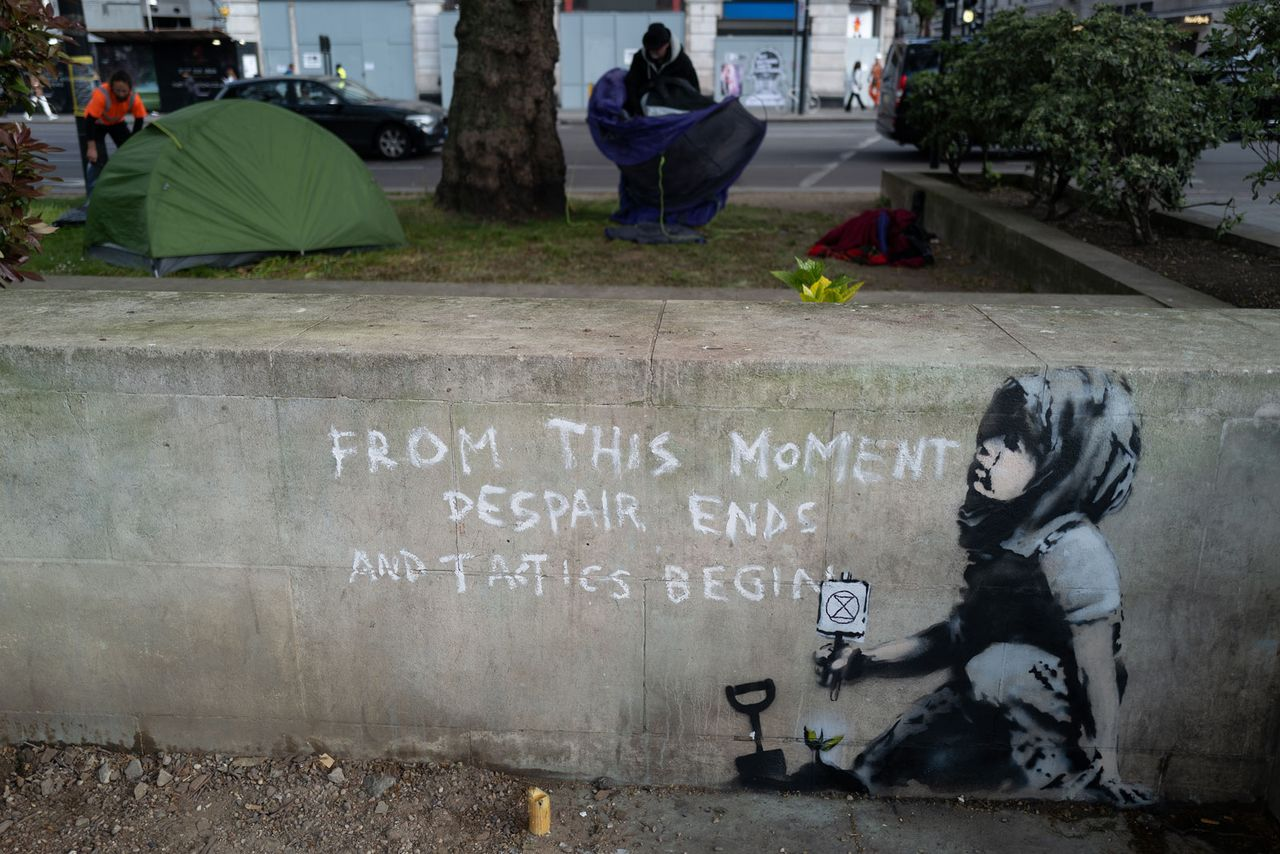 """A new piece of street art believed to be by Banksy appeared on 26 April in London.  The works shows a child holding a small Extinction Rebellion sign crouching by a newly-planted seedling with the words """"From This Moment Despair Ends And Tactics Begin"""" Photo: Leon Neal/Getty Images"""