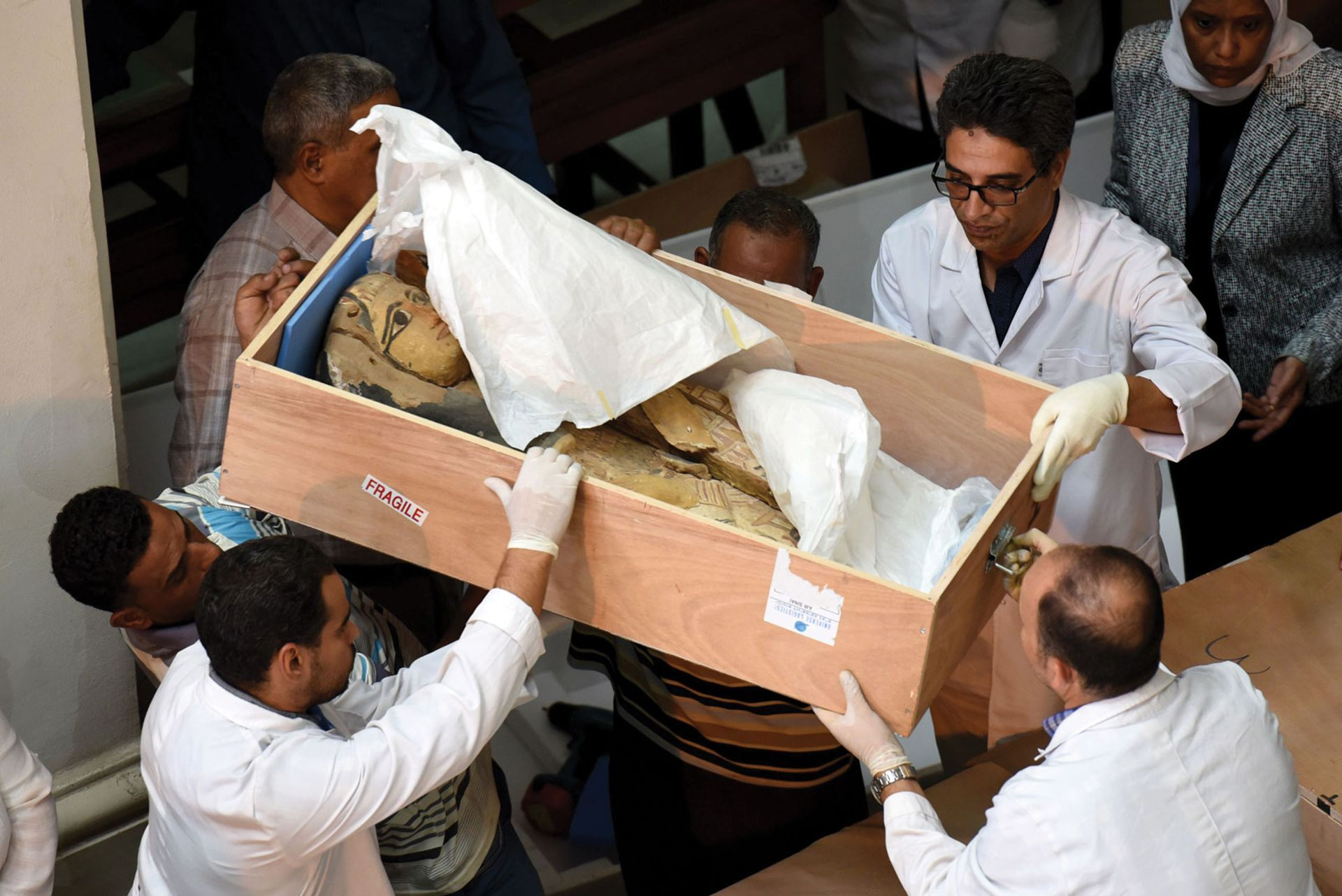 Egyptian museum staff with a sarcophagus repatriated by the Israeli government in 2016 after discovering it had been looted MOHAMED EL-SHAHED/AFP/Getty Images